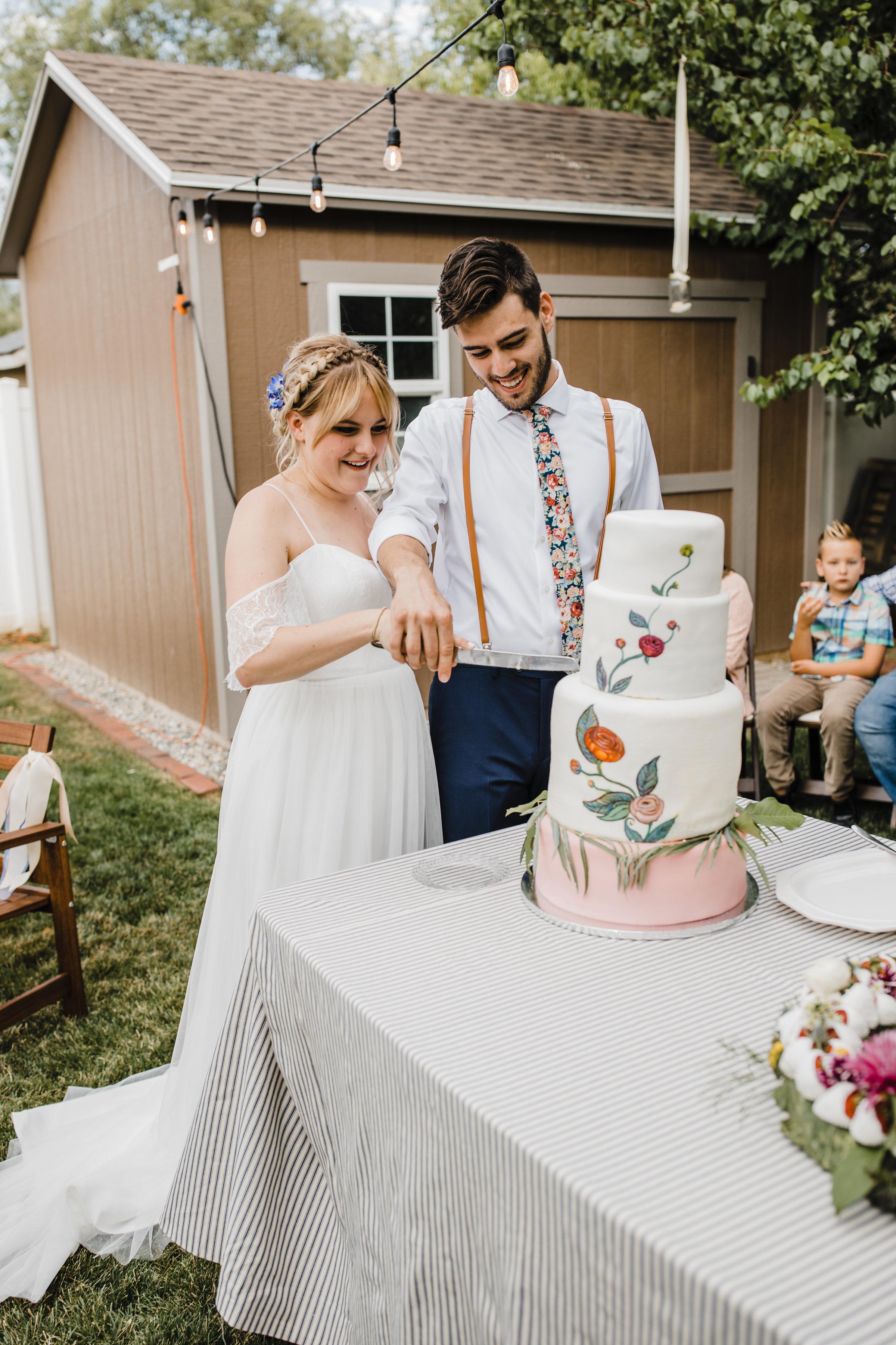 Salt Lake city utah wedding photographer cutting cake smiling floral painted cake