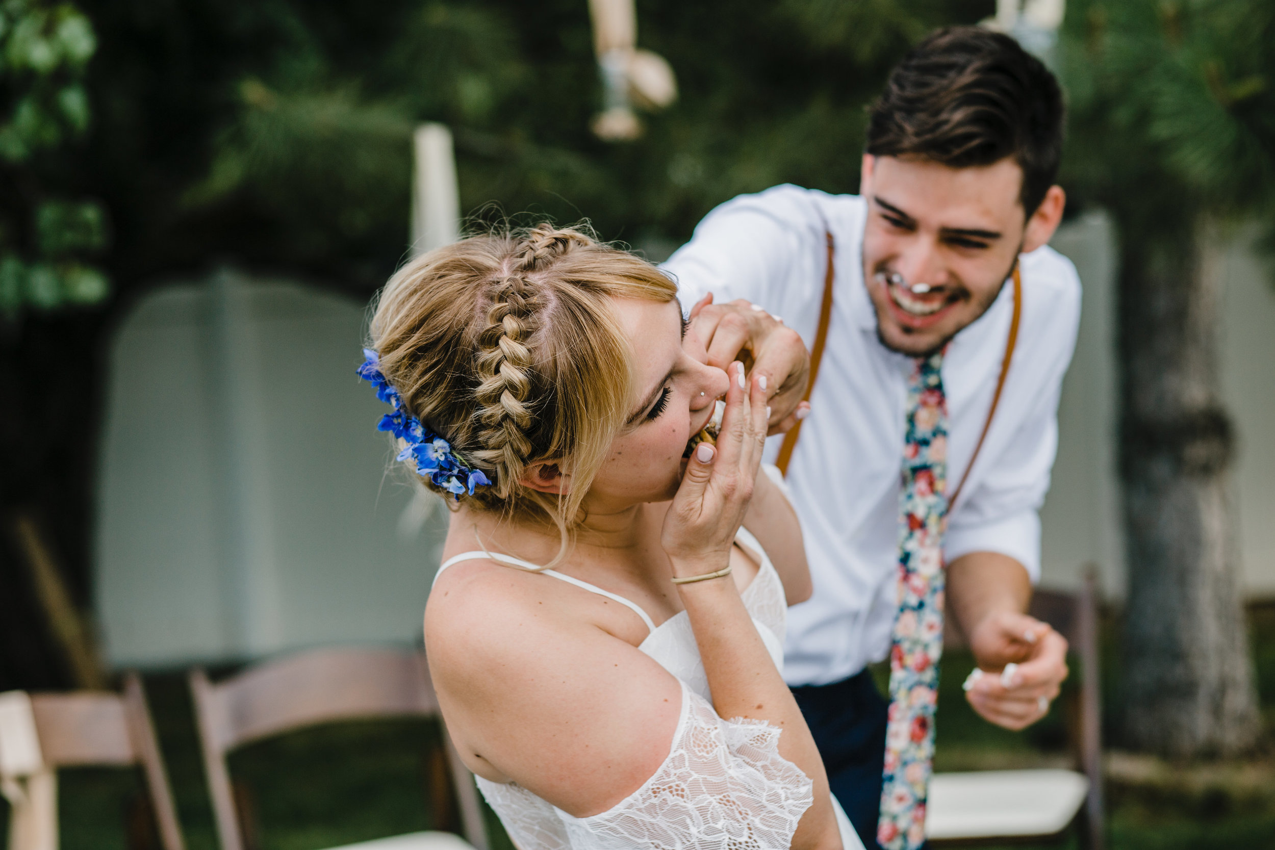 South jordan utah wedding photographer outdoor wedding reception bohemian bride braided wedding hair blue flower crown stuffing cake faces smiling