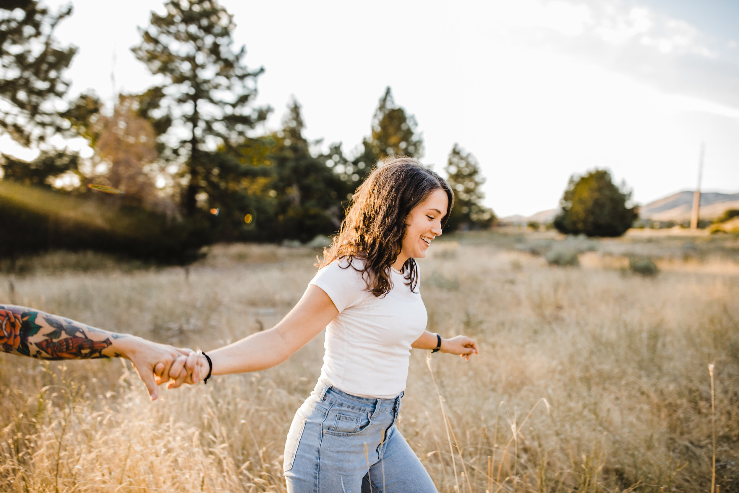 professional engagement photographer in cache valley utah holding hands running exploring happy fields
