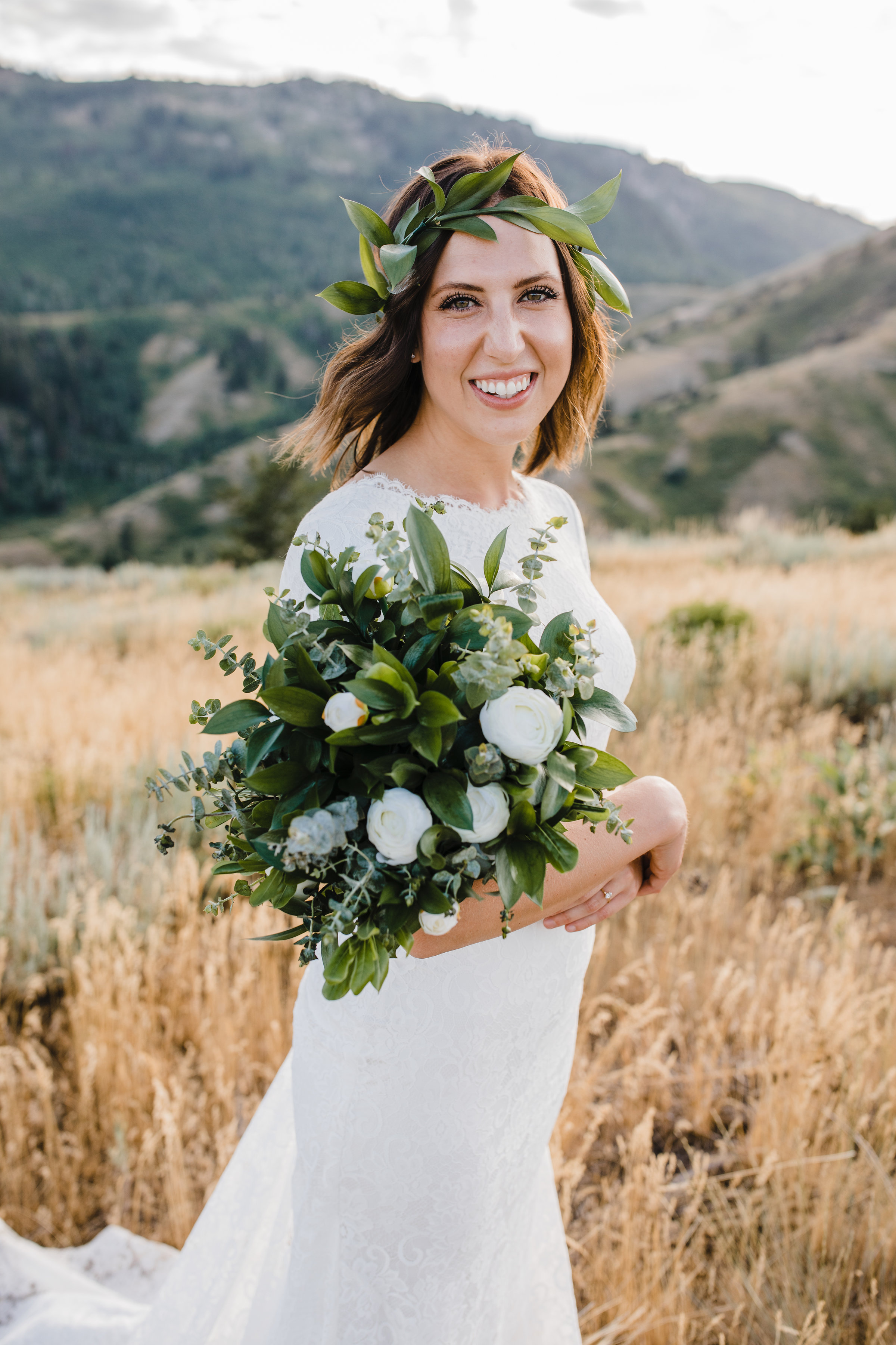 bridal photographer in brigham city utah smiling mountains field floral crown bohemian bouquet