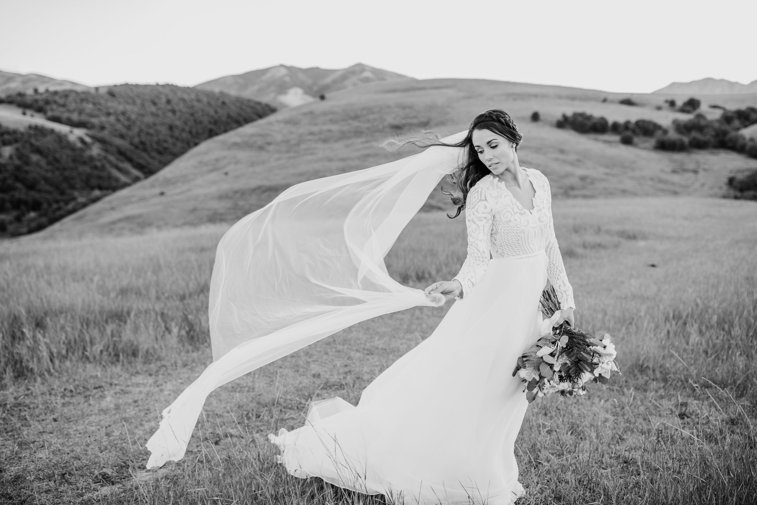 adventurous wedding photographer windblown veil lace dress