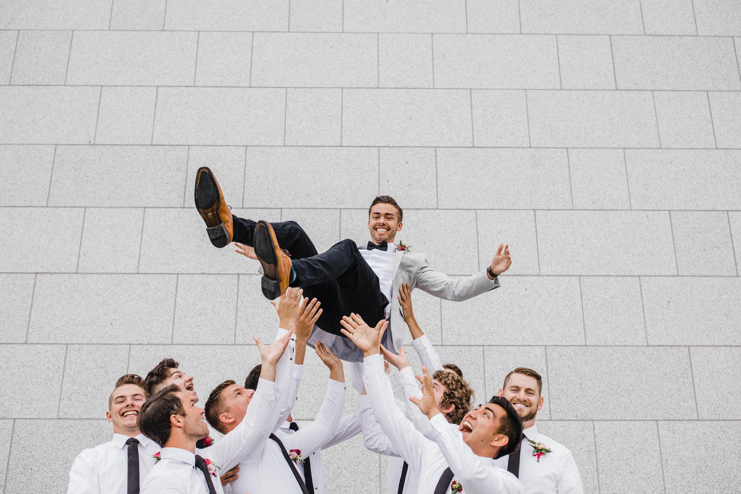 professional wedding photographer in utah valley utah groomsmen lift happy laughing
