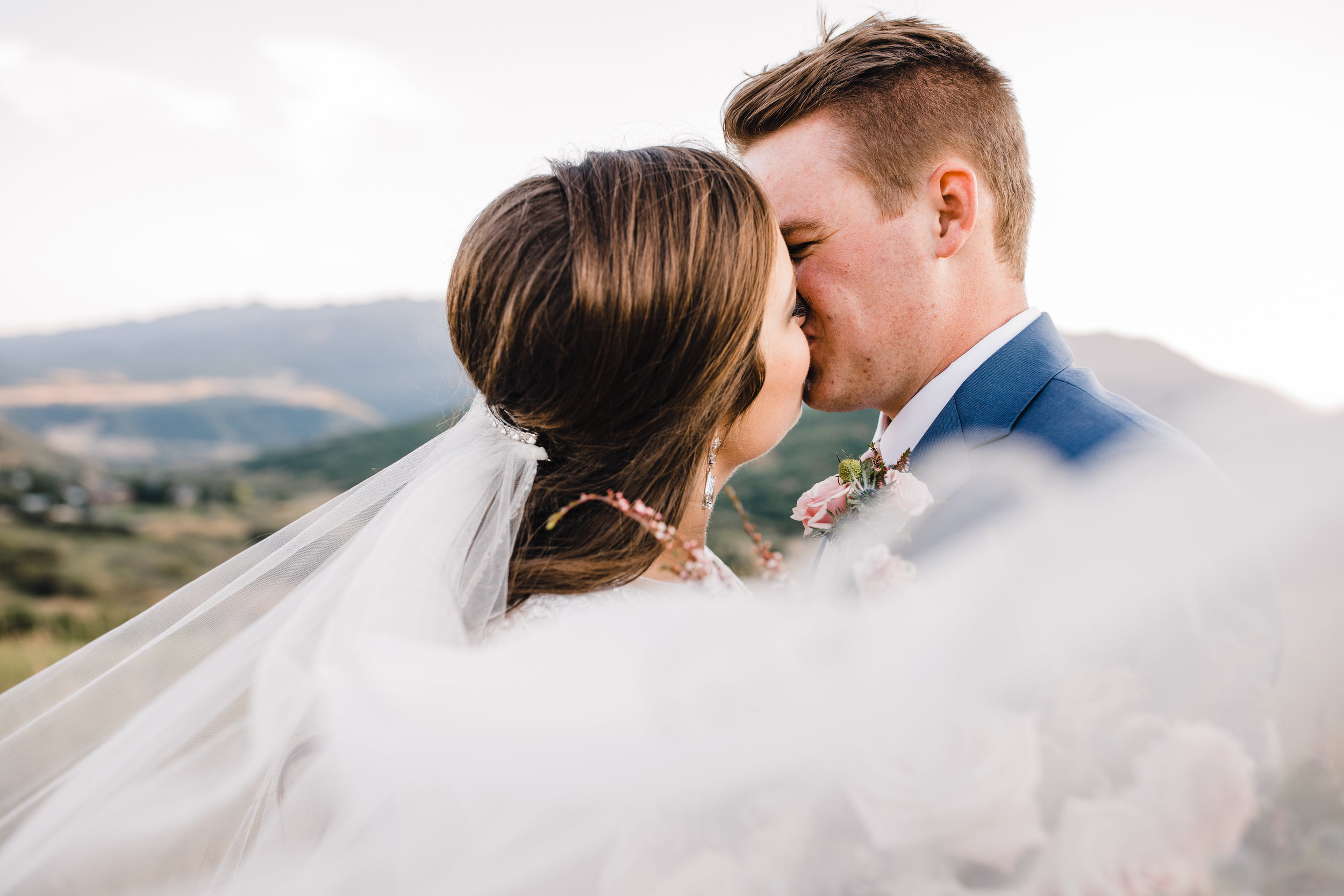 professional wedding photographer in cache valley windy veil kissing romantic pink bouquet