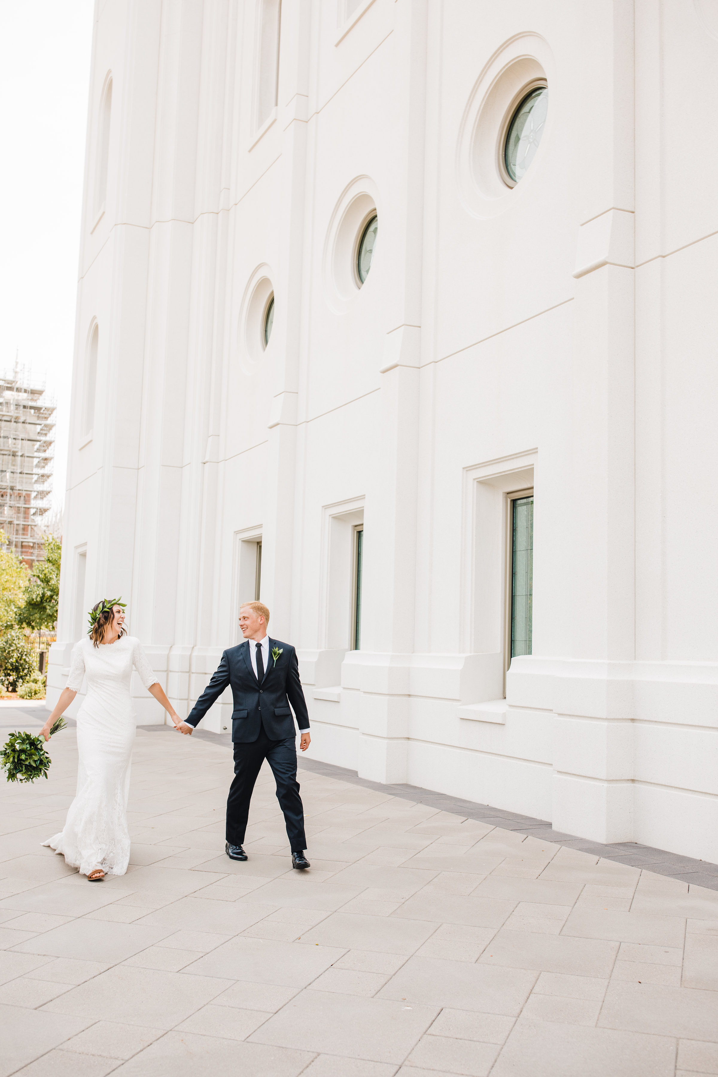 professional wedding photographer in brigham city holding hands lds temple wedding exit walking
