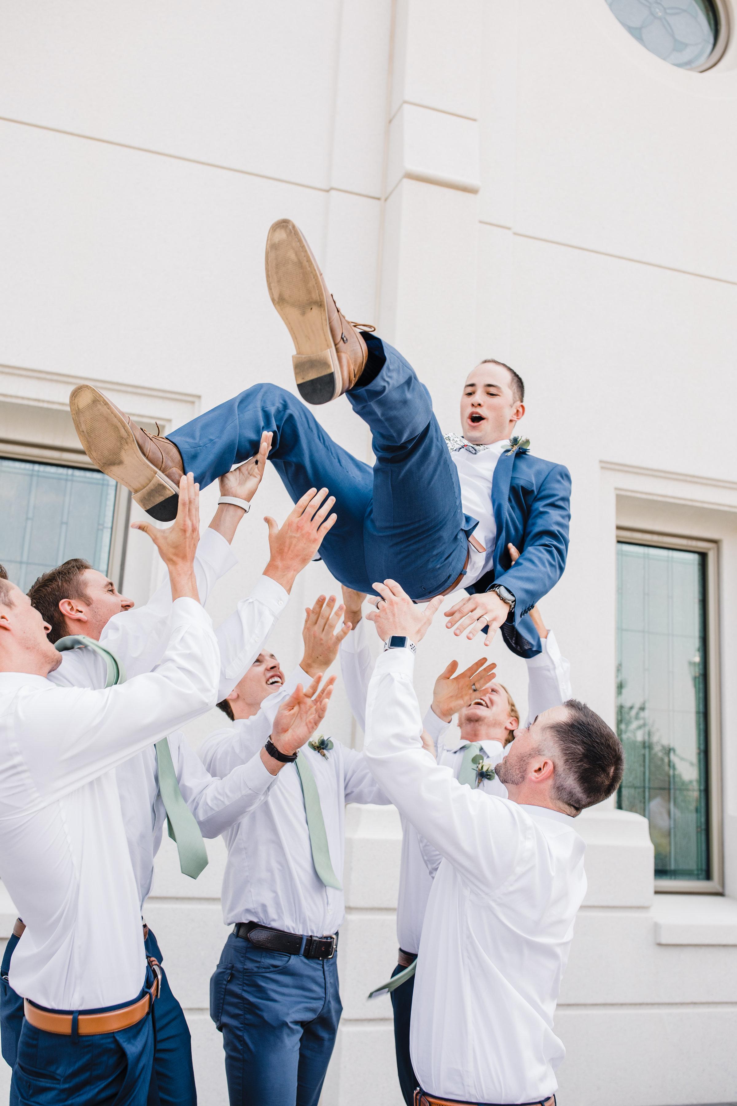 best photographer in brigham city utah groomsmen throwing groom happy cheering navy suit