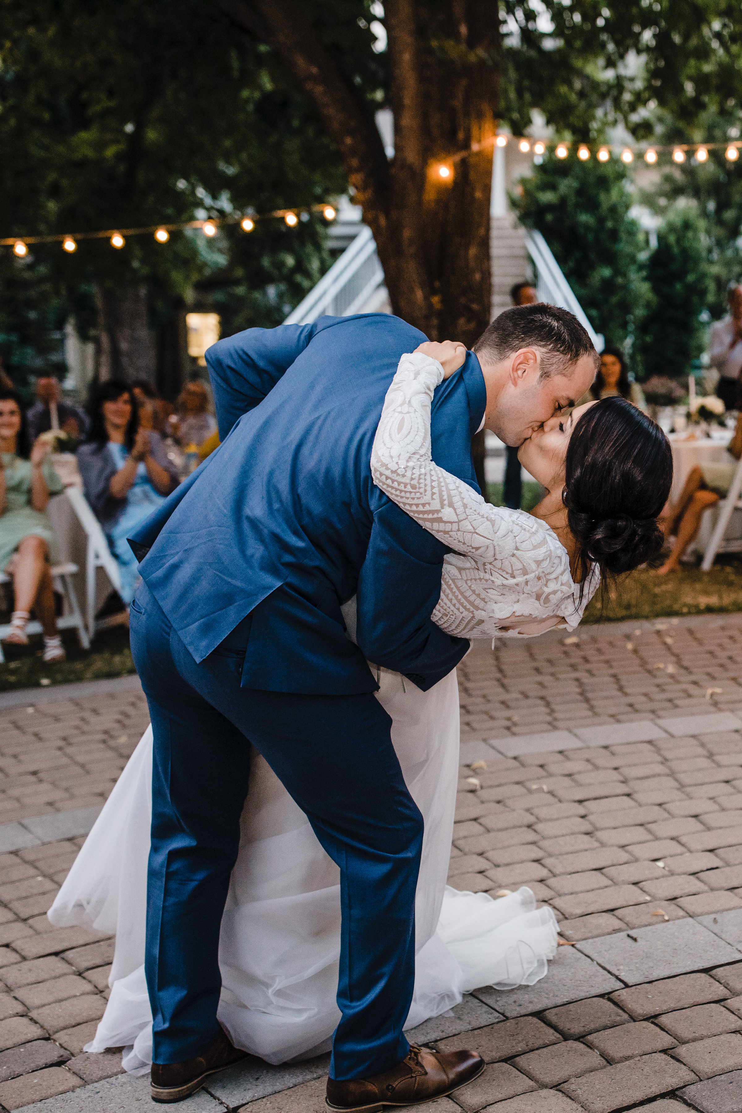 brigham city utah wedding photographer outdoor reception string lights dipping first dance kissing