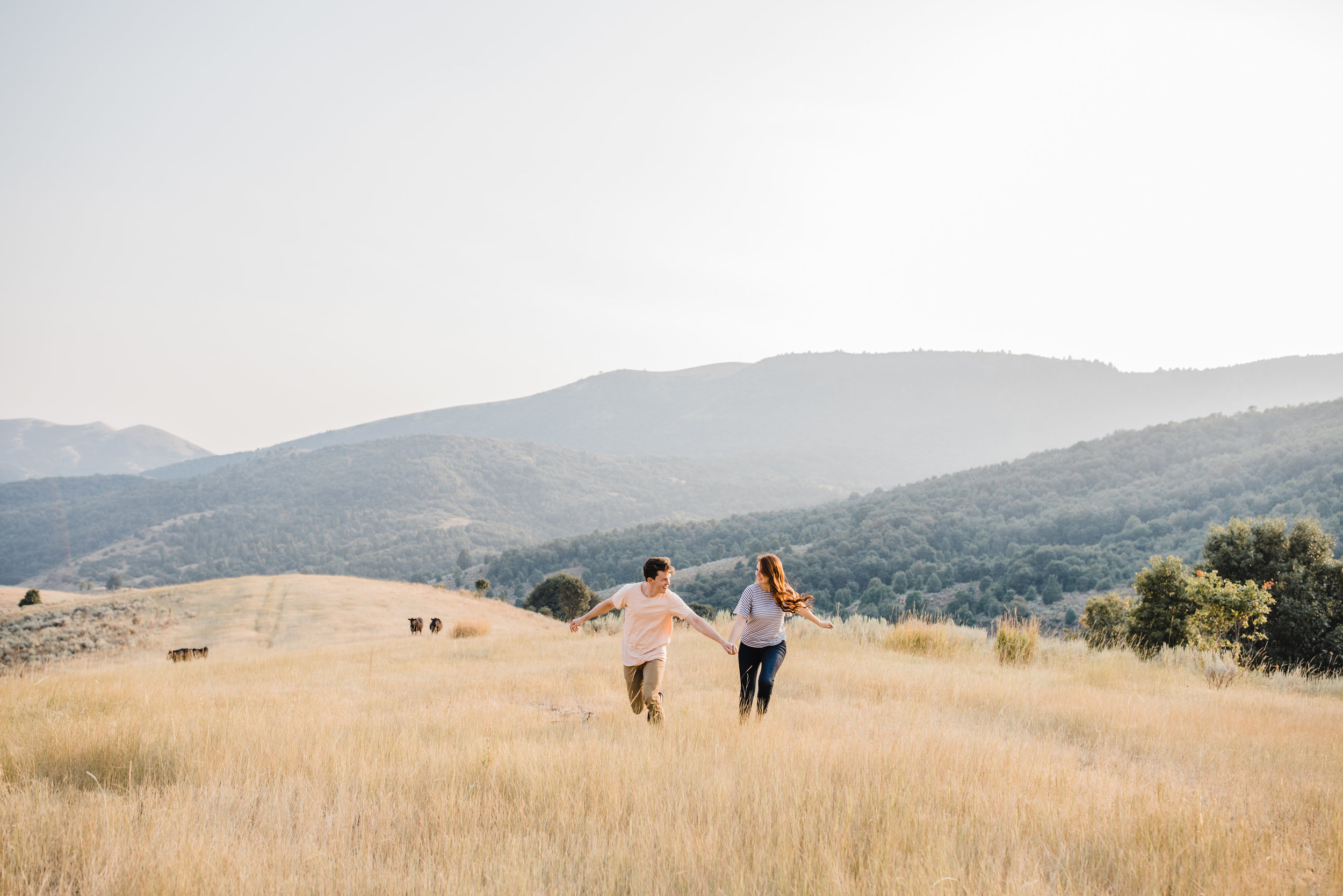 engagement photographer sardine canyon holding hands running laughing fields mountains