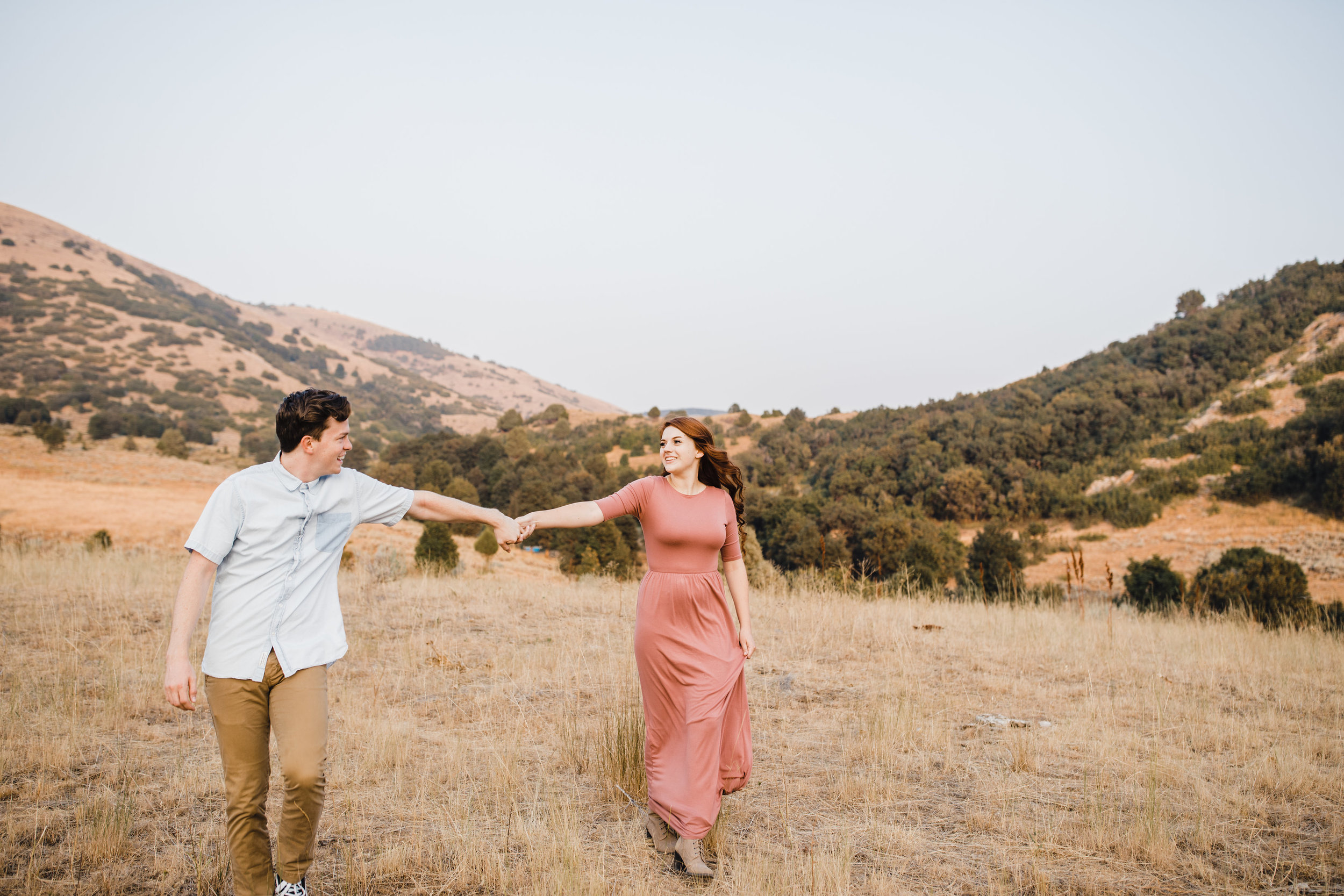 engagement photographer in sardine canyon utah holding hands walking mountain backdrop