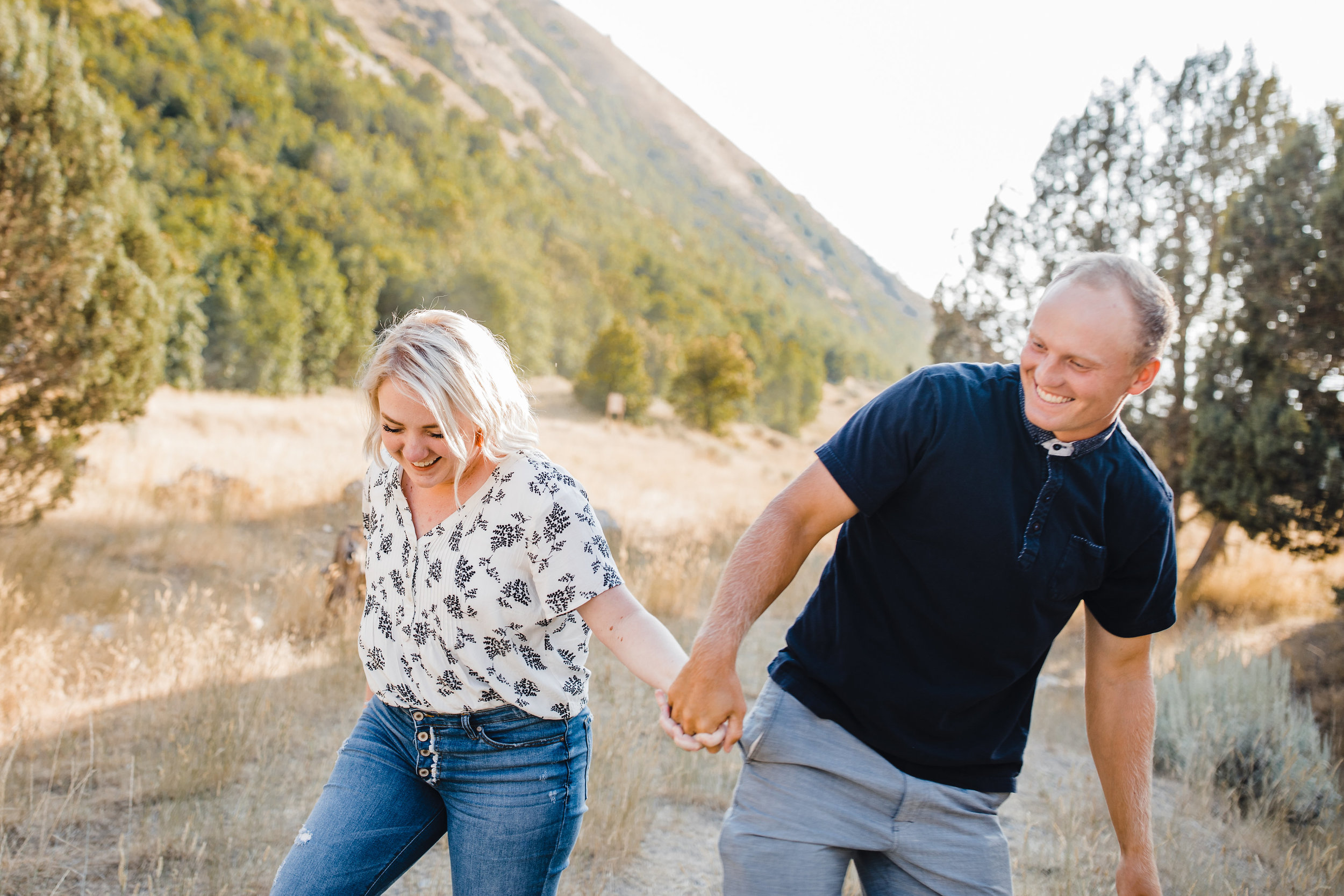 cache valley professional couples photographer laughing holding hands walking mountain backdrop