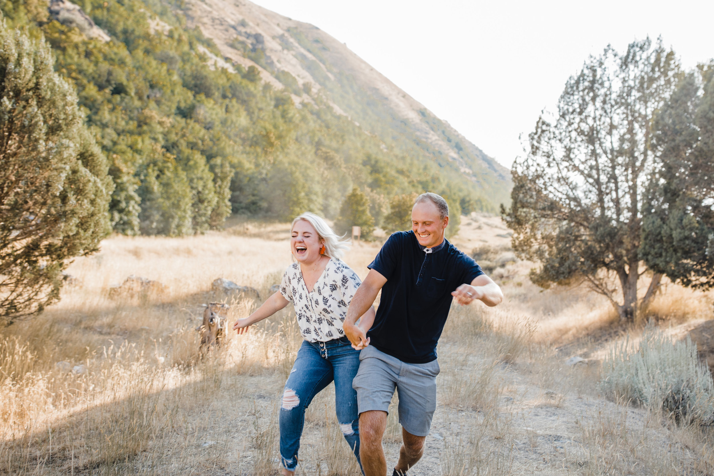 cache valley professional couples photographer best laughing holding hands mountain backdrop running nose crinkle