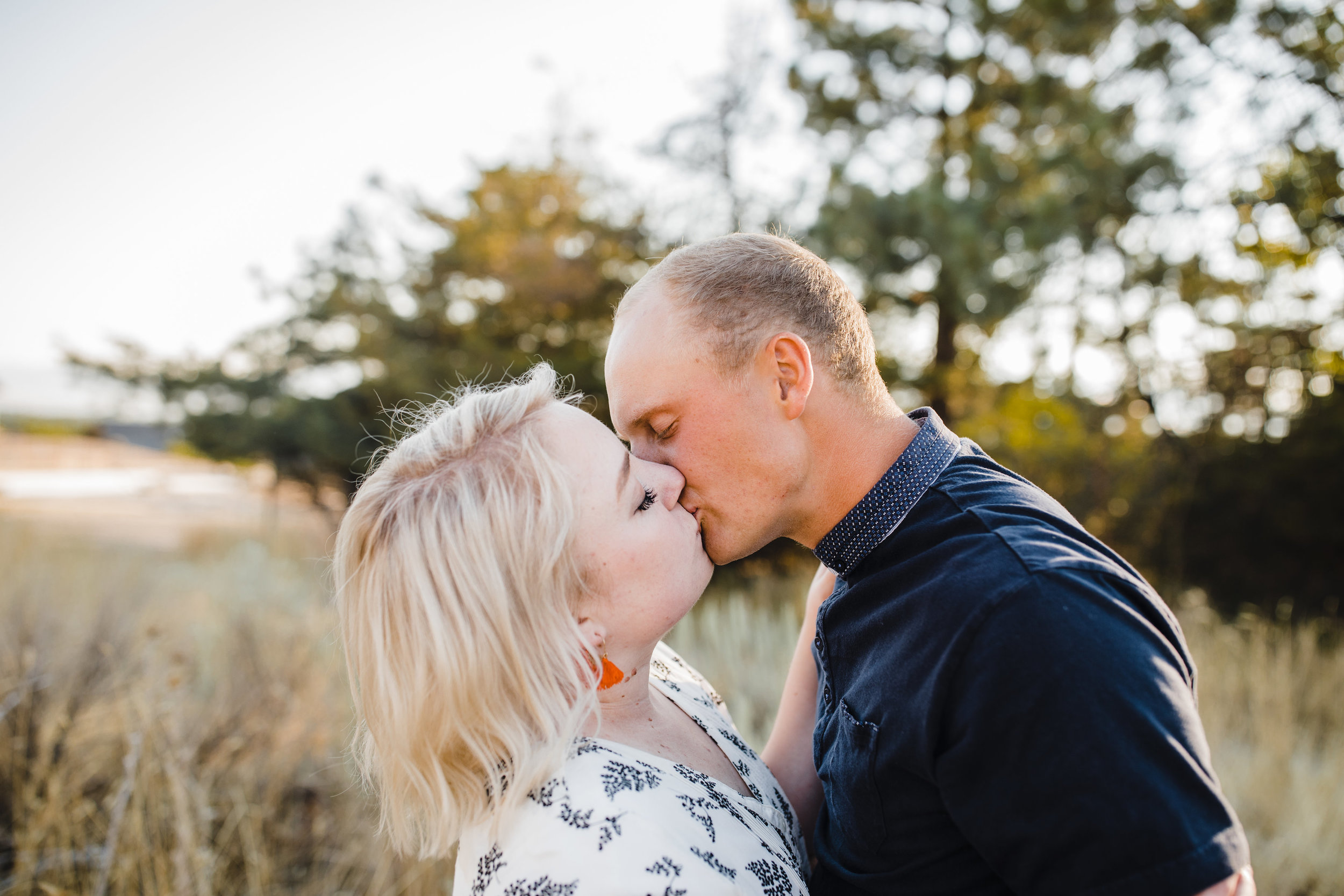 professional logan utah couples photographer kissing field backdrop romantic