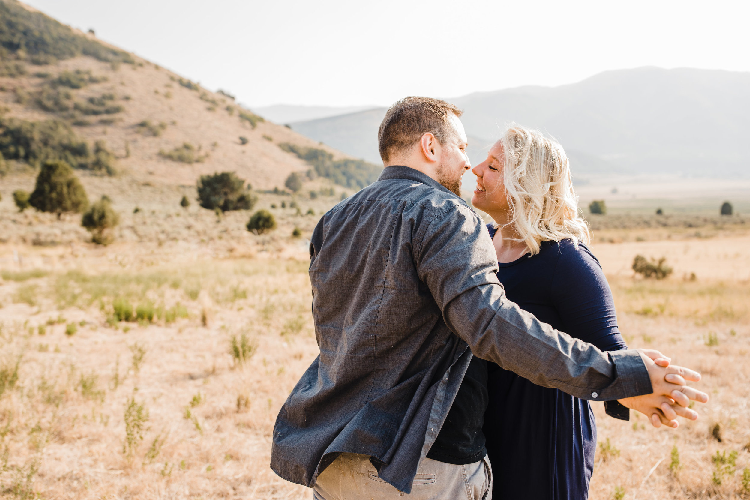 mantua utah engagement photographer mountain backdrop slow dancing laughing windblown
