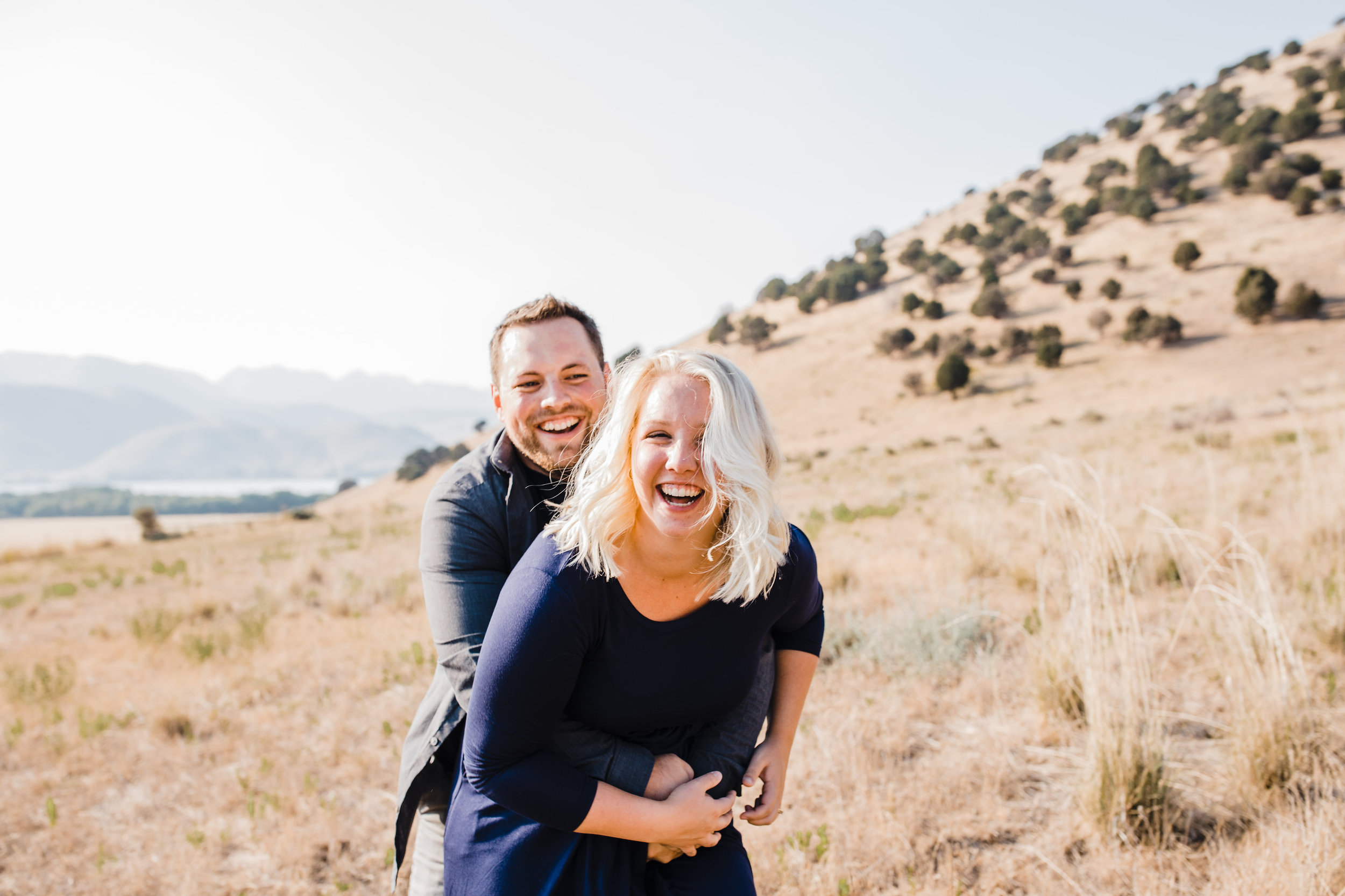 brigham city professional engagement photographer mountain backdrop laughing hugging running