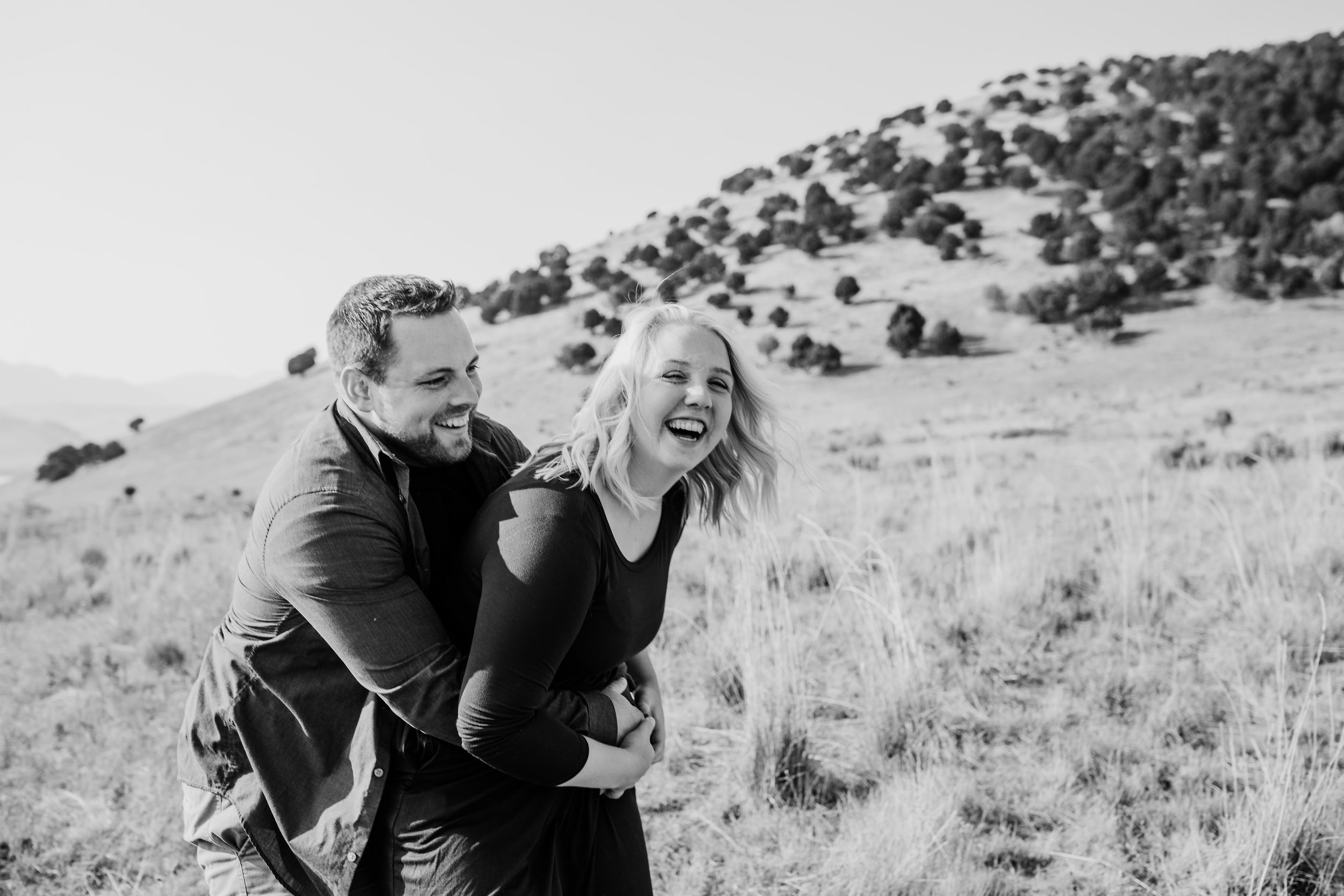 engagement photographer in brigham city utah hugging mountains laughing playful