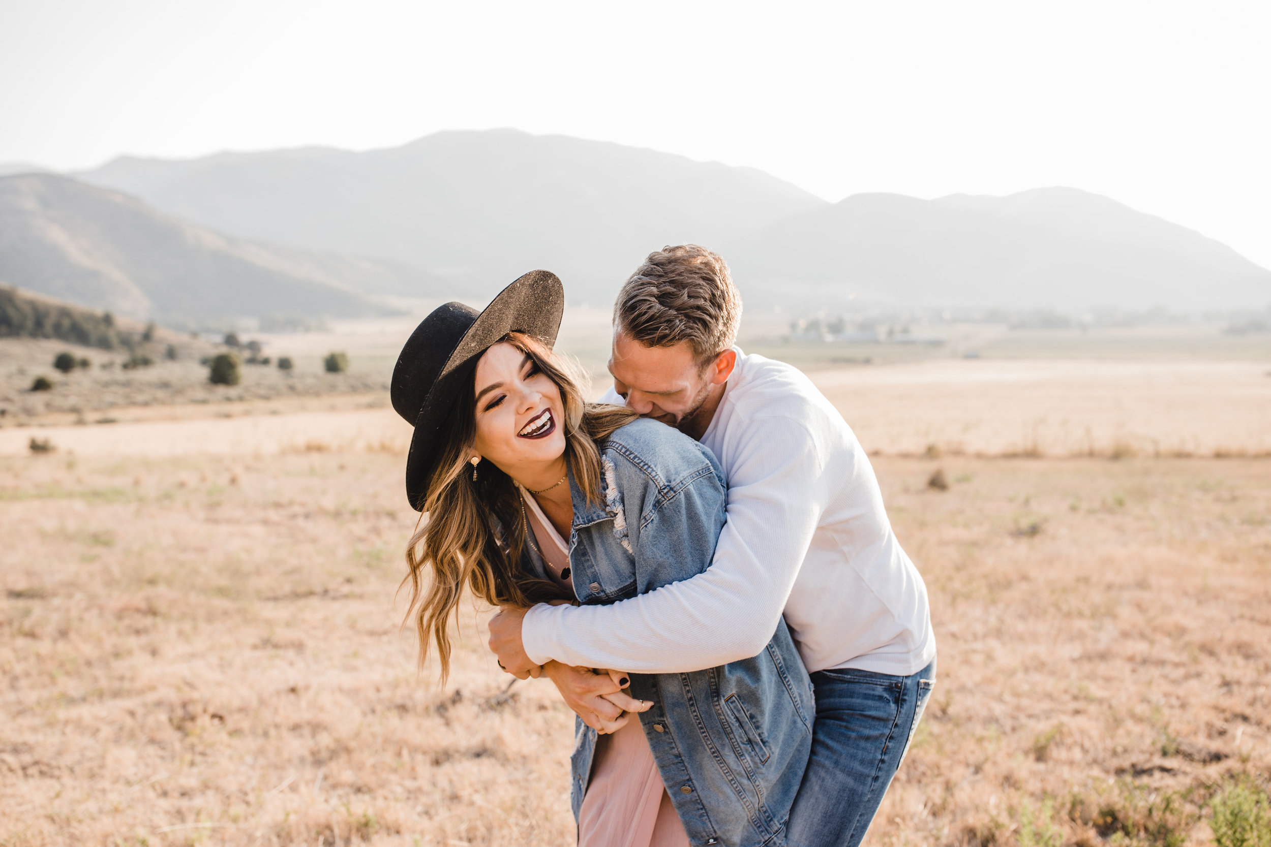 professional couples photographer in mantua utah mountains fields sunhat hugging playful laughing