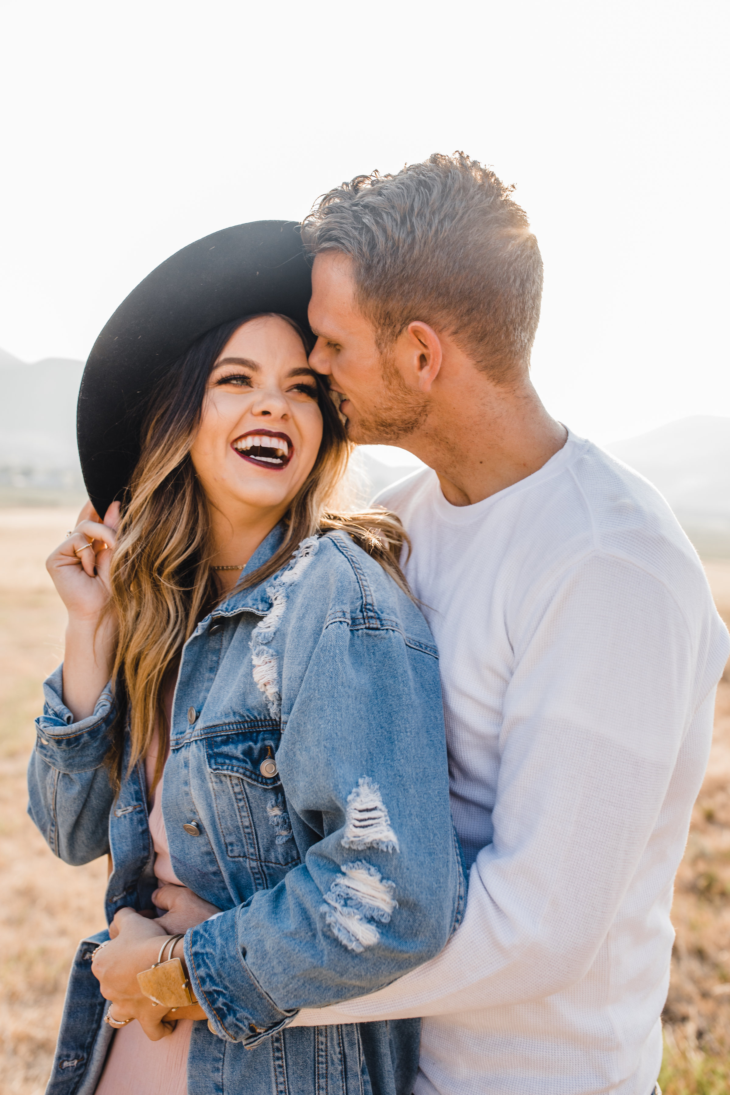 best couples photographer in mantua utah hugging laughing sunhat