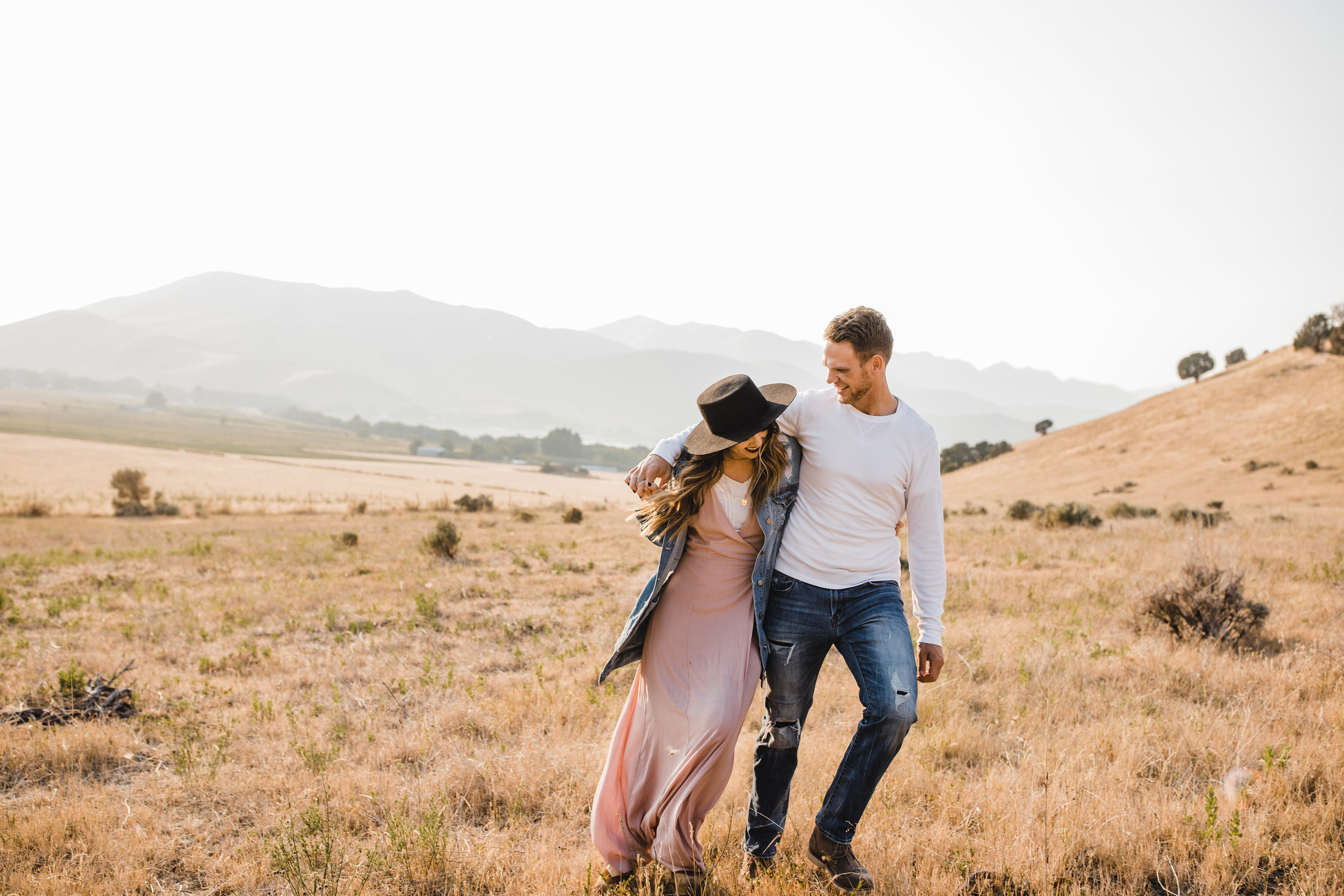 best mantua utah couples photographer hugging walking windblown mountains sunhat