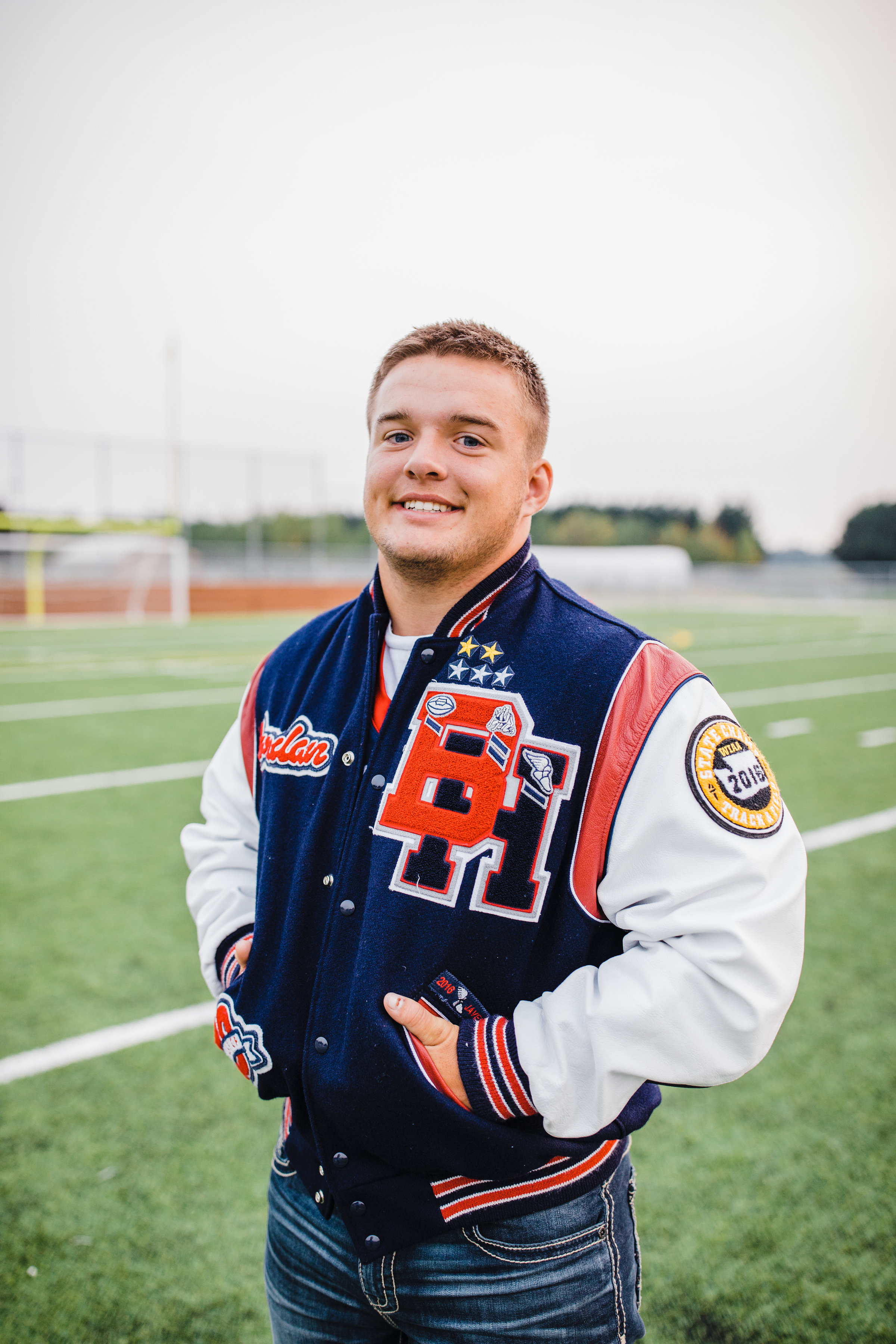 professional senior photo photographer football smiling football jacket field smiling