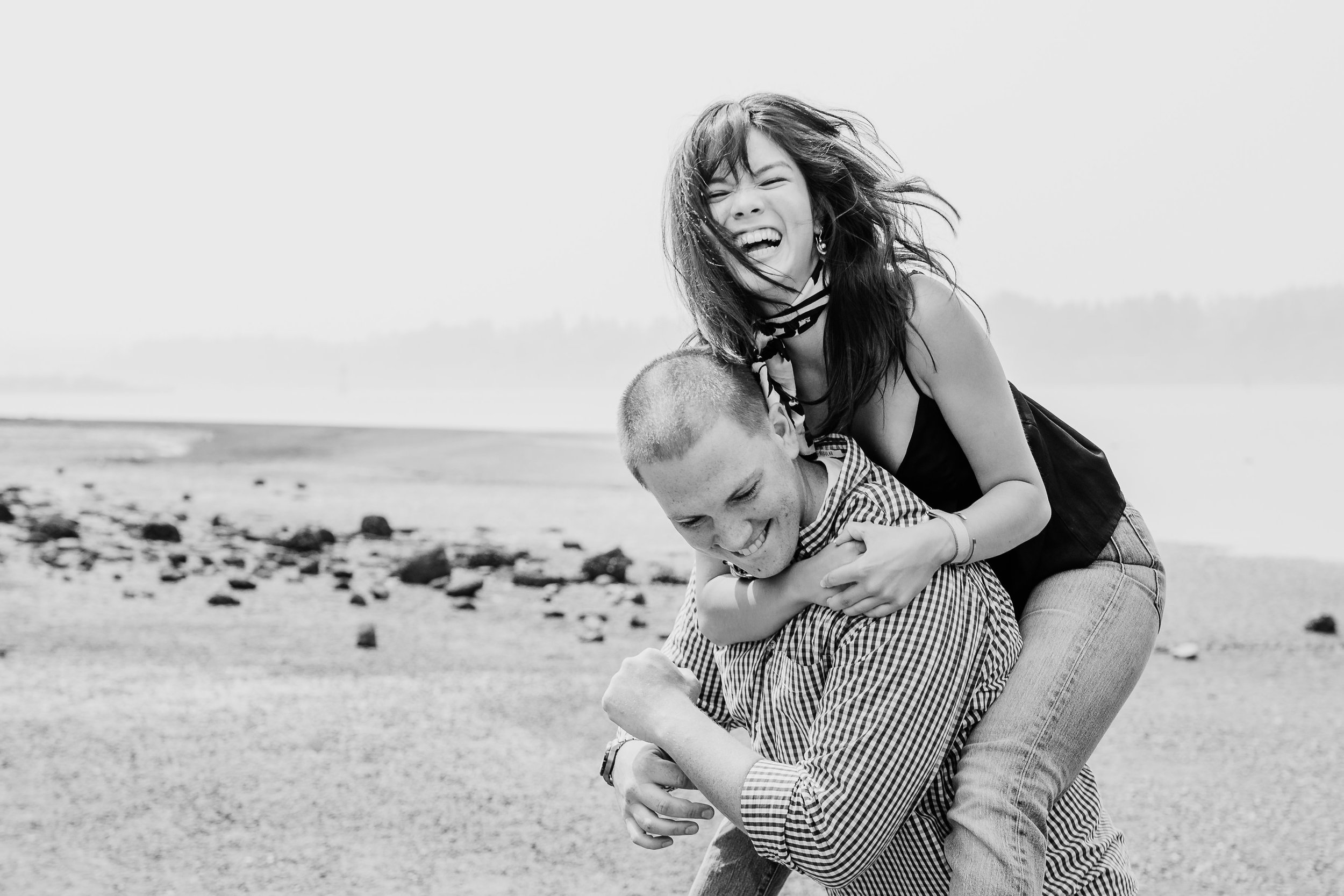 best professional engagement photographer in olympia washington beach smiling playful kissing piggy back