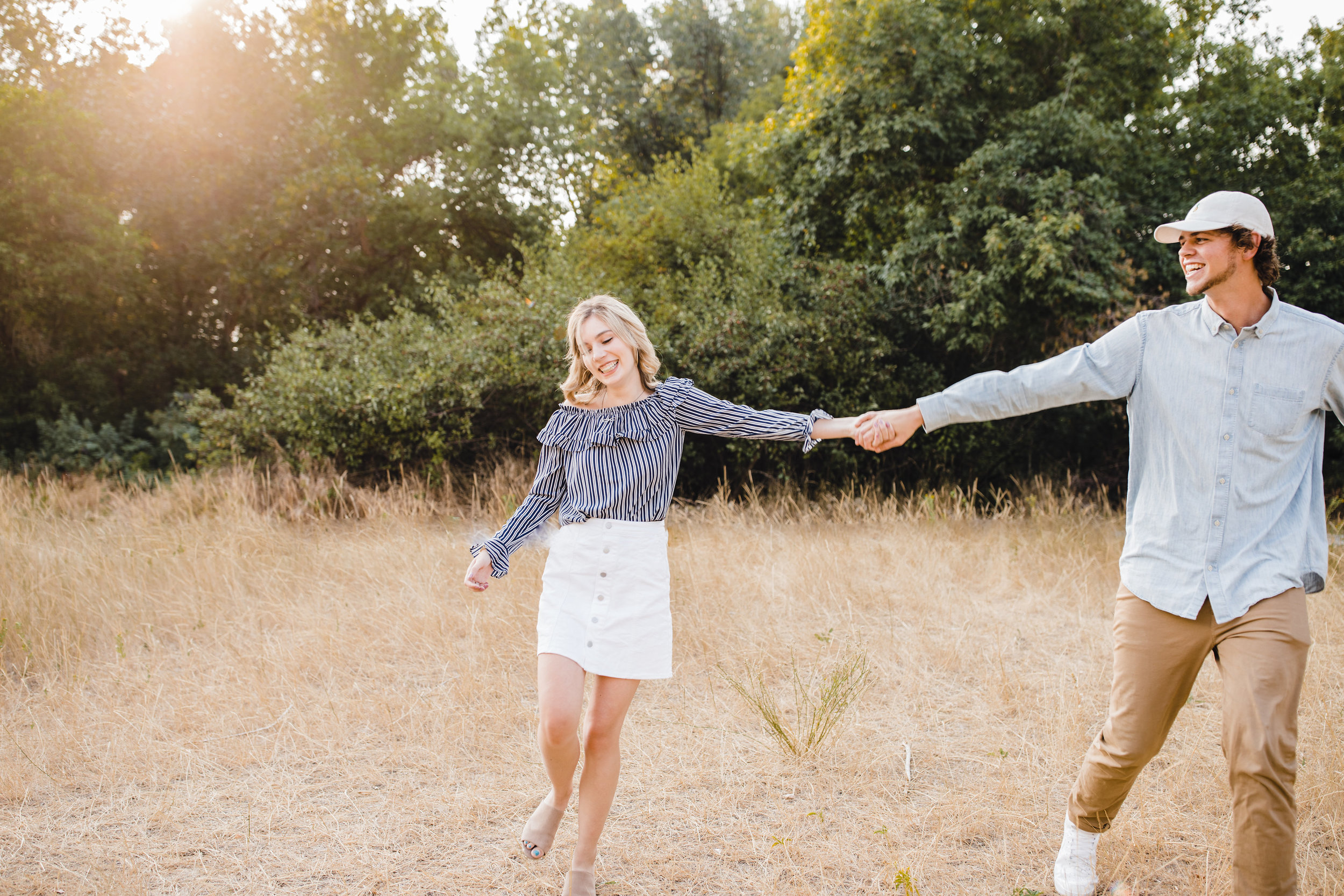 professional couples photographer in cache valley utah holding hands walking laughing field