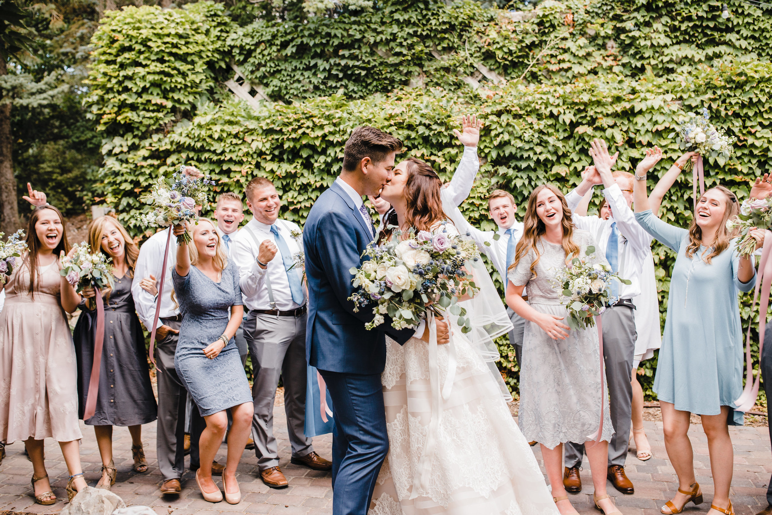 best professional wedding photographer in utah valley wedding party neutral dresses cheering happy kissing