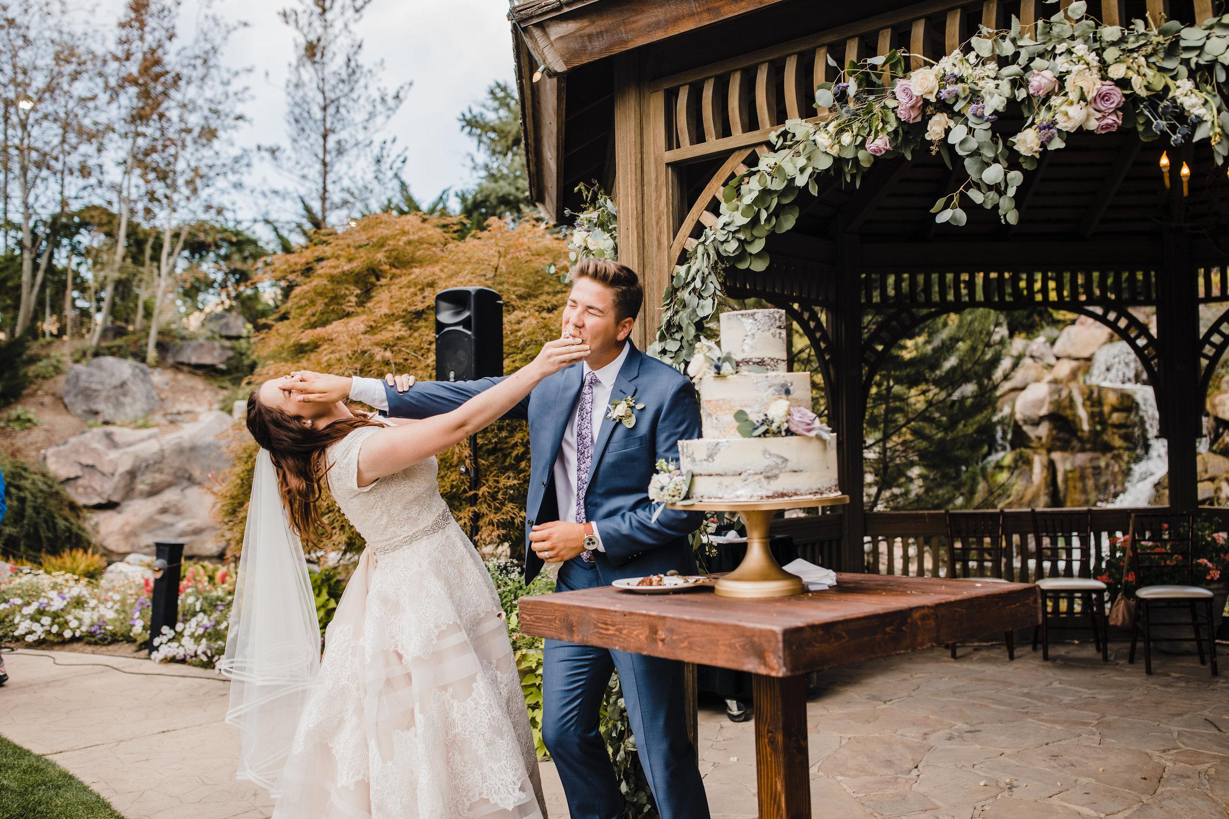 provo utah wedding photographer cake cutting outdoor reception smashing playful