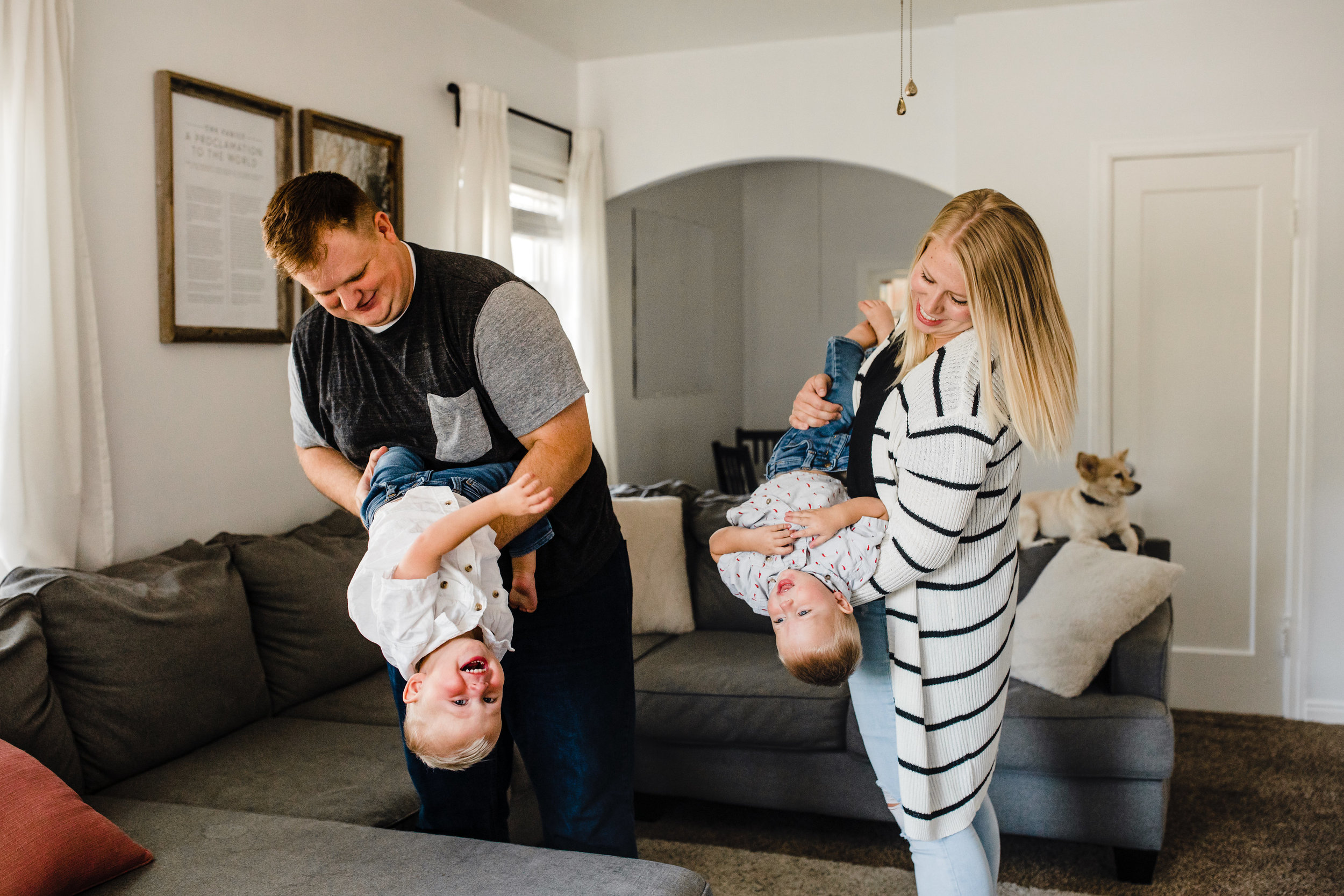 professional lifestyle photographer in logan utah living room twin boys toddlers playful upside down holding