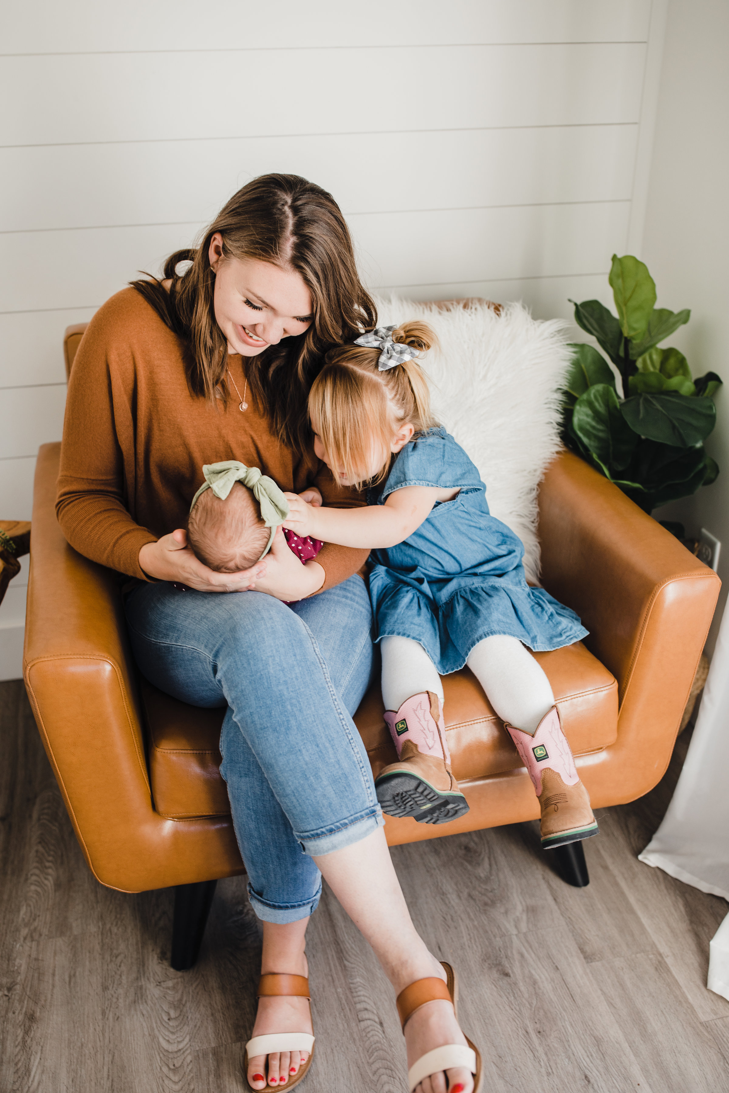 best lifestyle photographer cache valley utah station studio leather chair fur pillow neutral outfits mom big sister holding baby