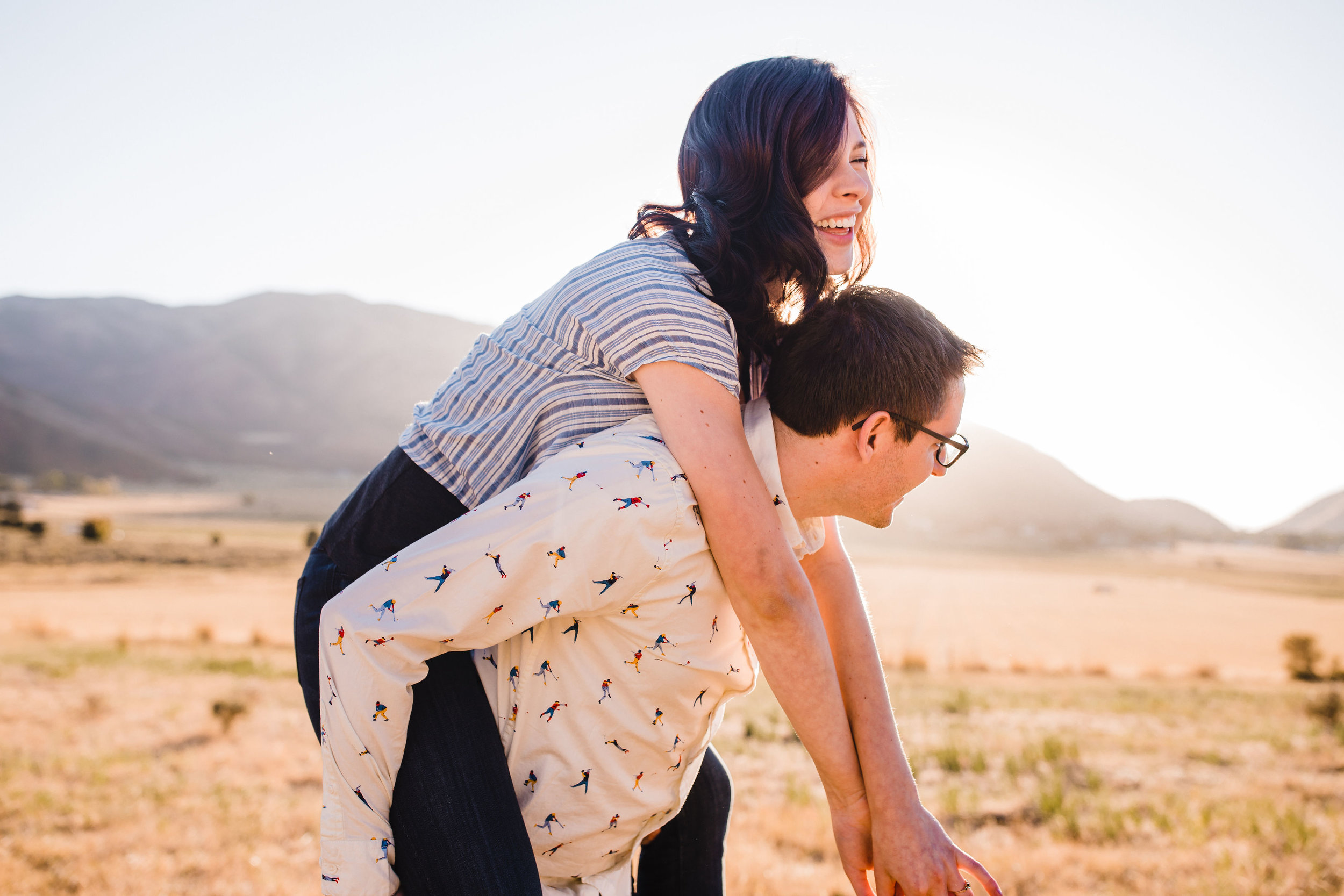 logan utah engagement photographer piggy back laughing playful mountains field