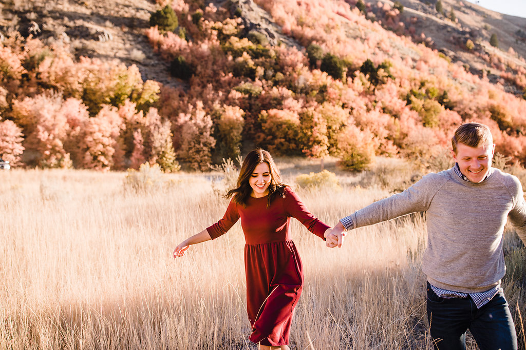 logan utah engagement photo shoot red dress fall leaves running through fields green canyon wild grass wind blowing through hair romantic engagement photos