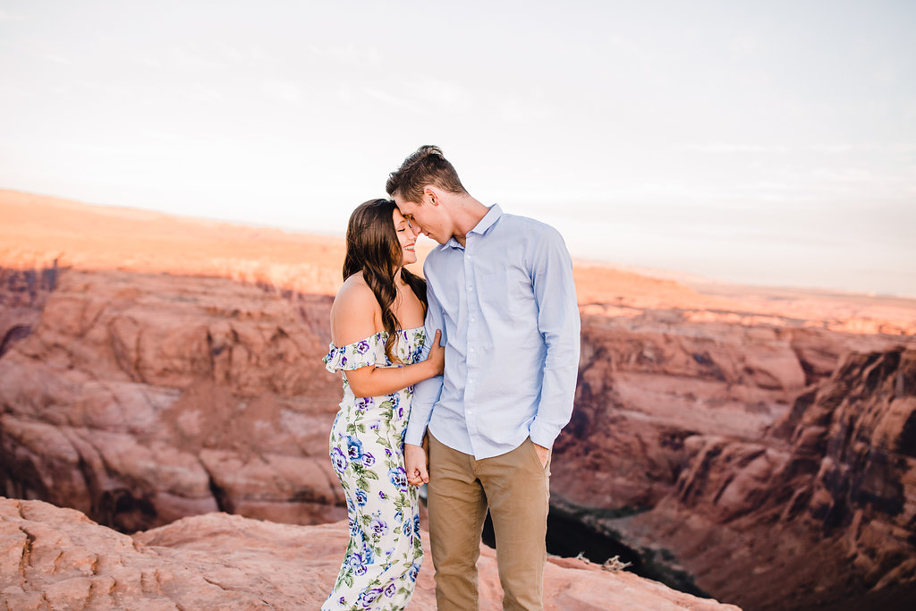 grand canyon professional couples photographer hugging smiling romantic sunset red rocks