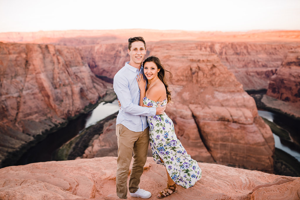 horseshoe bend professional photographer grand canyon red rocks cliffs hugging smiling sunset