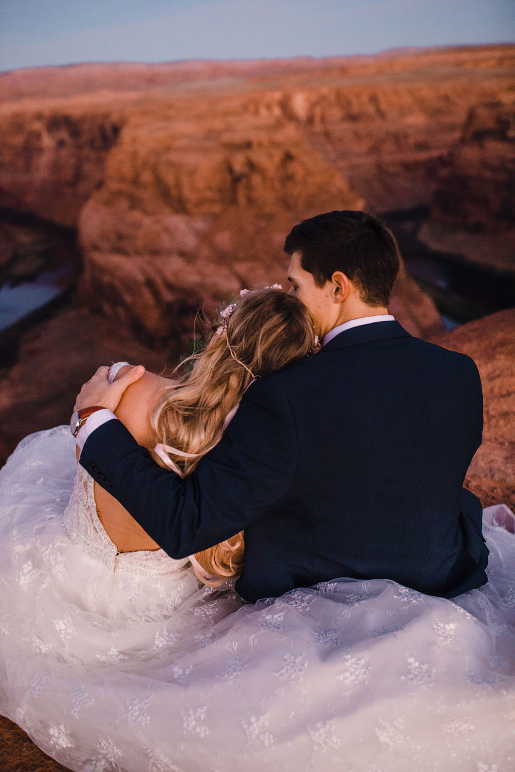 professional formal photographer page arizona red rocks grand canyon sitting hugging romantic wedding dress train
