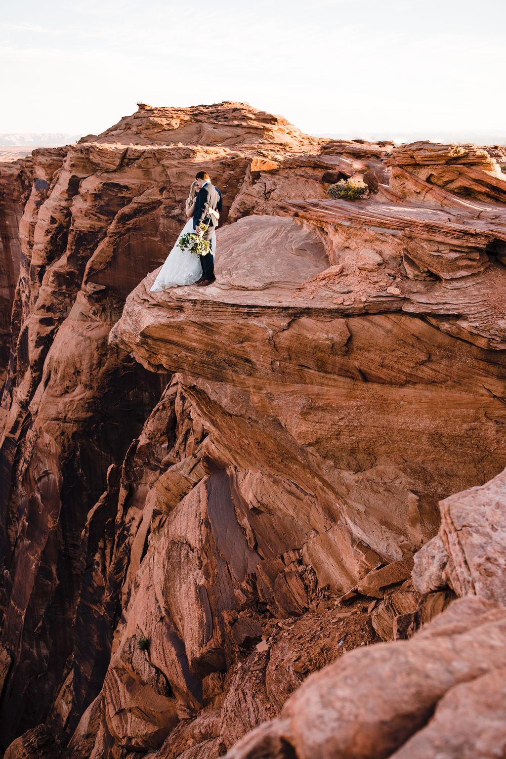 horseshoe bend formal photographer red rocks cliff white bouquet bohemian bride