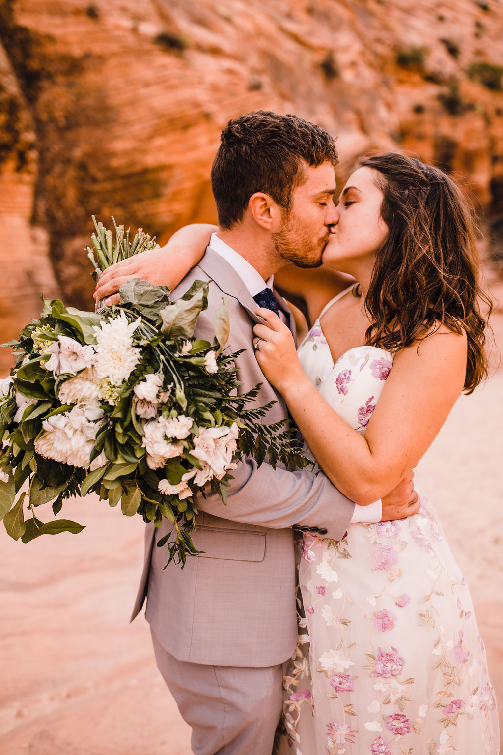 professional page arizona formal photographer pink floral wedding dress white bouquet kissing red rocks horseshoe bend