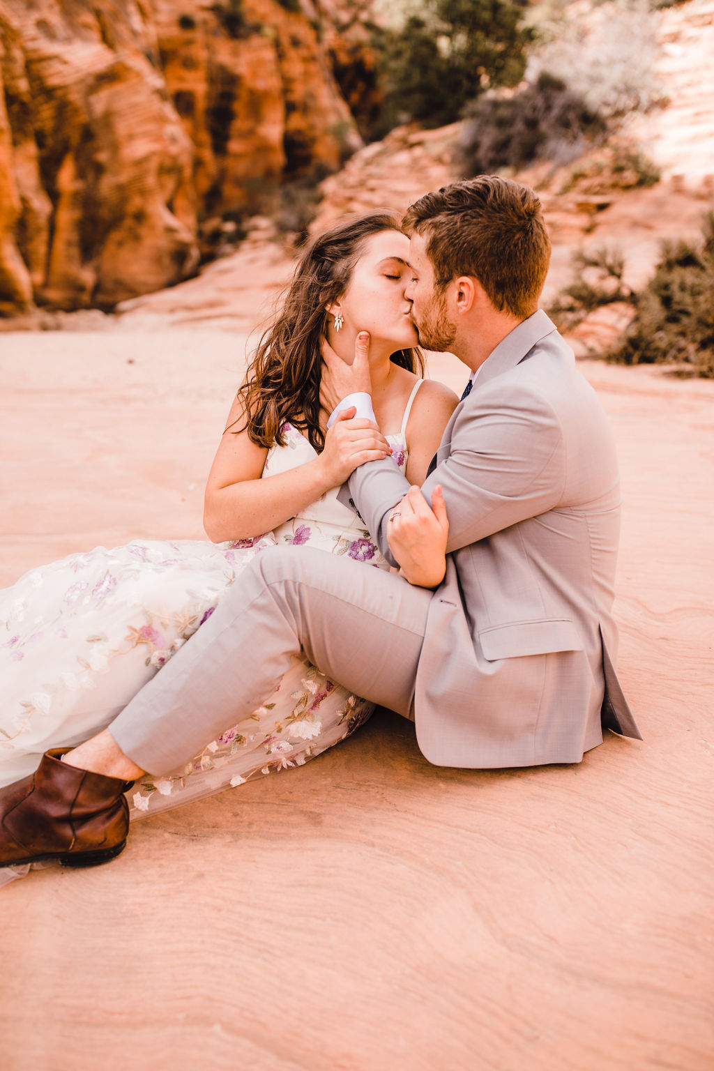 best page arizona formal photographer sitting cuddling red rocks sand pink floral wedding dress kissing romantic