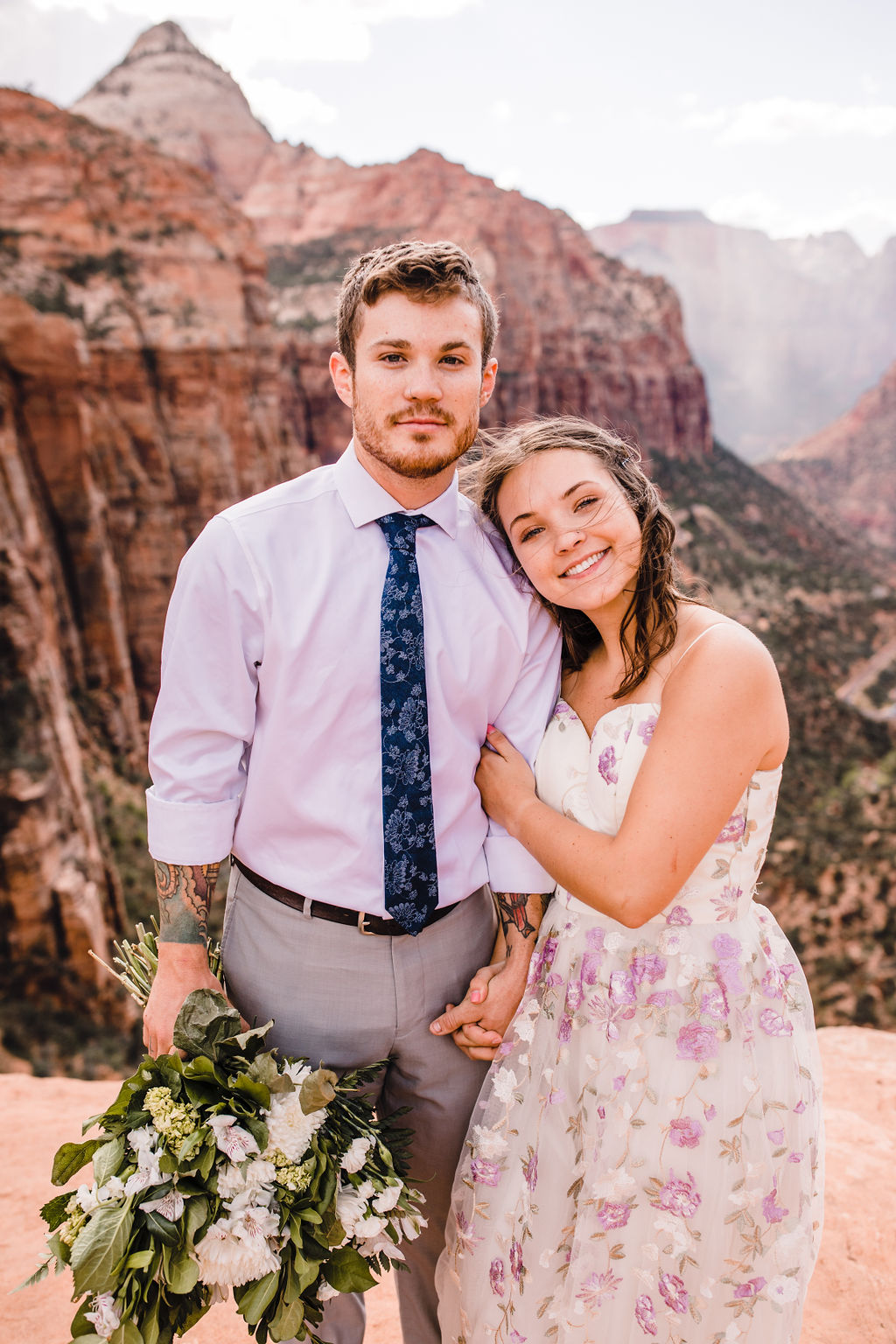 best grand canyon formal photographer pink floral wedding dress red rocks hugging cliff smiling