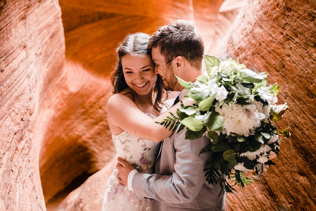 professional horseshoe bend formal photographer adventure red rock slots purple floral wedding dress white bouquet hugging smiling laughing
