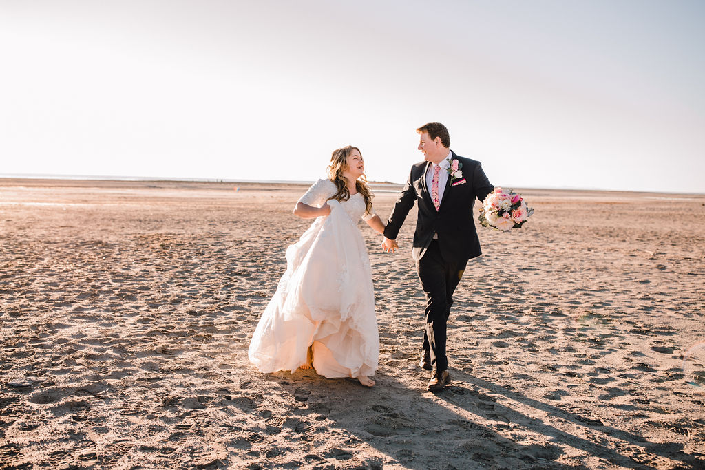 running holding hands romantic playful sunset antelope island salt lake city professional wedding formal photographer barefoot