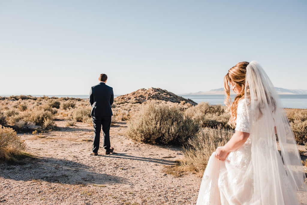first look long veil lace wedding dress antelope island great salt lake clear blue skies best formal photographer in utah valley