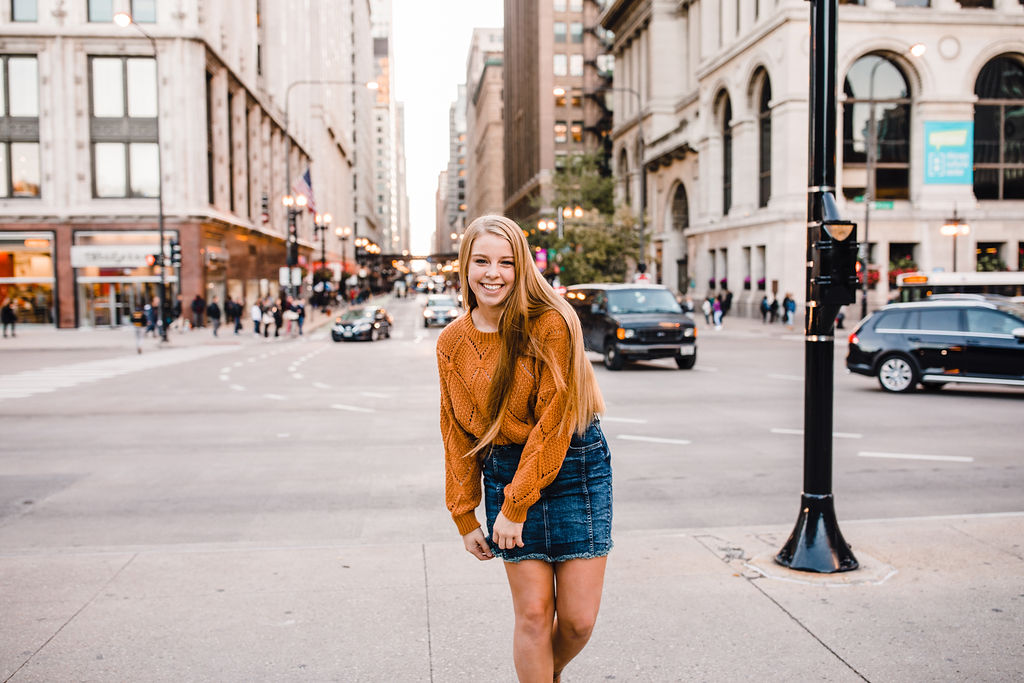 city scape sky scraper senior portrait photographer denim skirt busy street playful smile