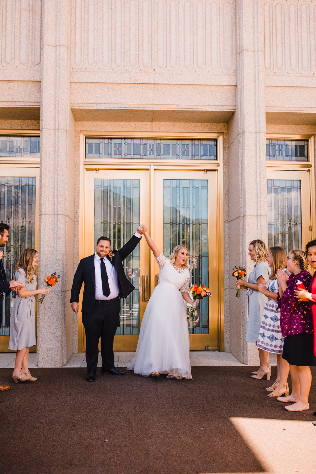 wedding exit holding hands cheering happy orange bouquet professional wedding photographer ogden utah
