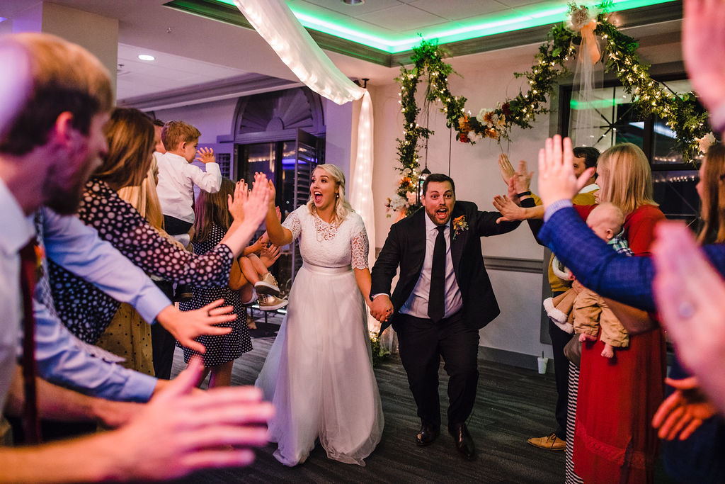 reception exit holding hands high fives running happy ogden utah wedding reception photographer