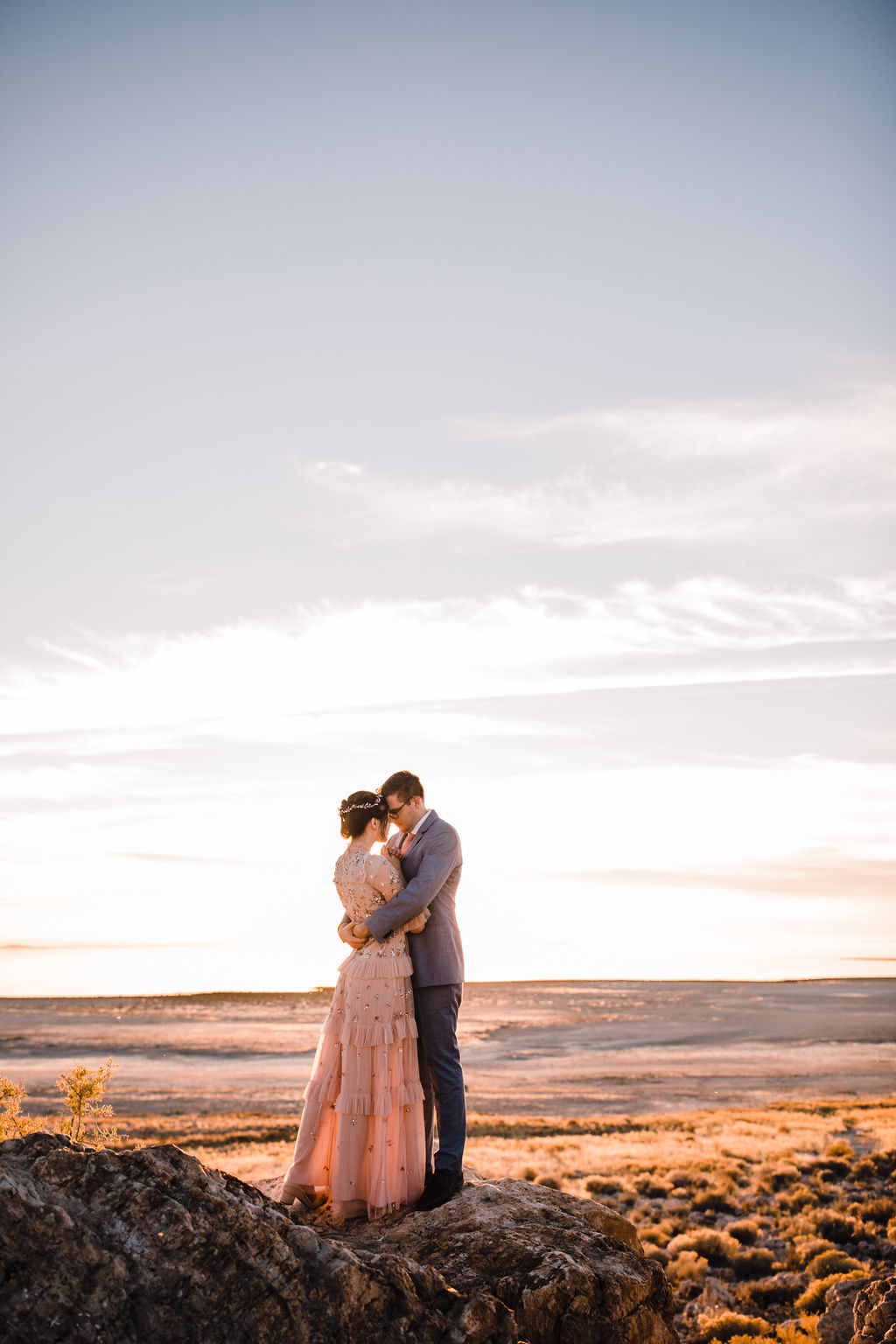 sunset wedding photos calli richards photography blush wedding dress with ruffles and jewels kissing couple bride and groom formals