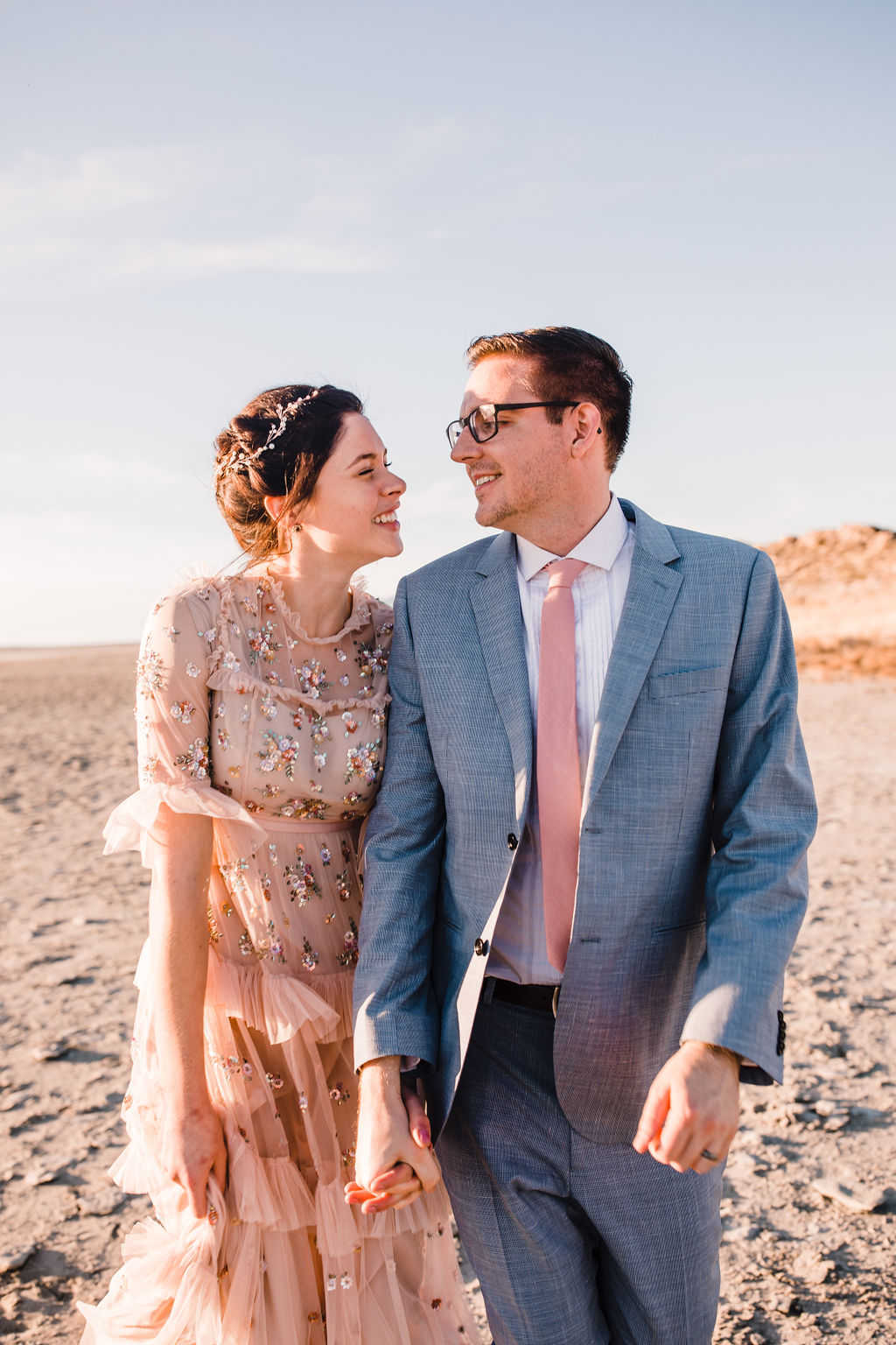 couple laughing walking sunset formals wedding photos bohemian wedding style braided hair grey suit holding hands bride and groom salt lake city wedding photographer calli richards