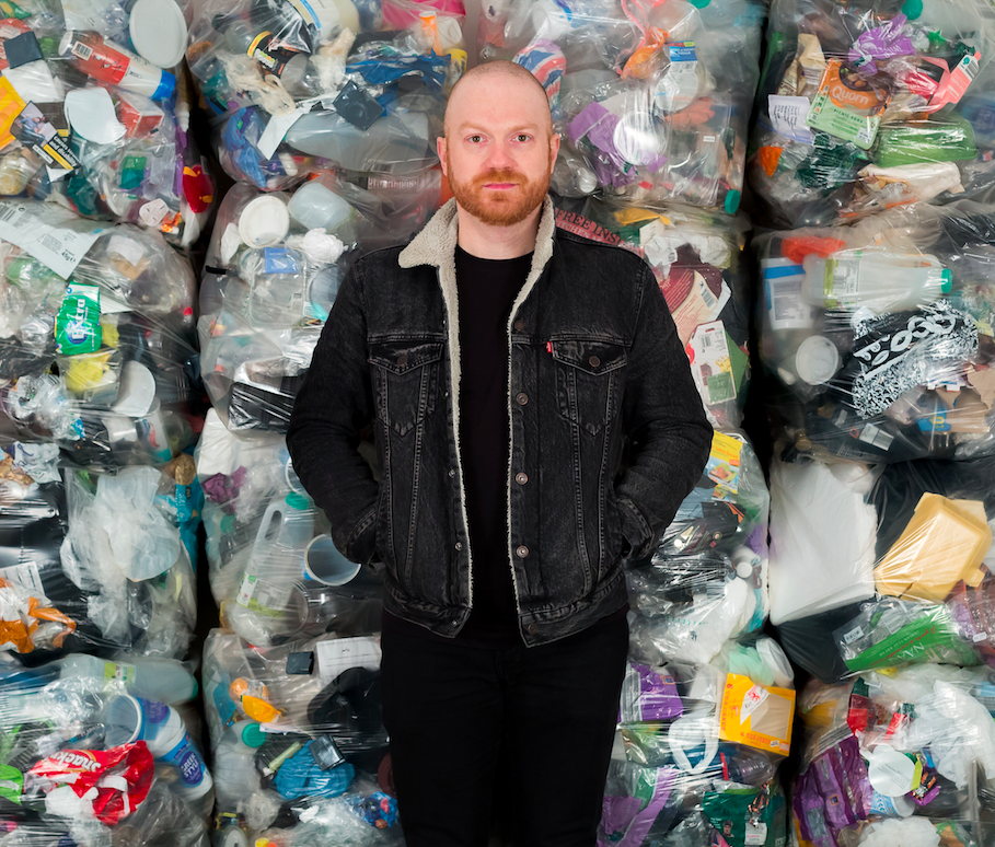 Daniel Webb in front of a portion of the plastic he personally used in one year -  Photograph by Ollie Harrop