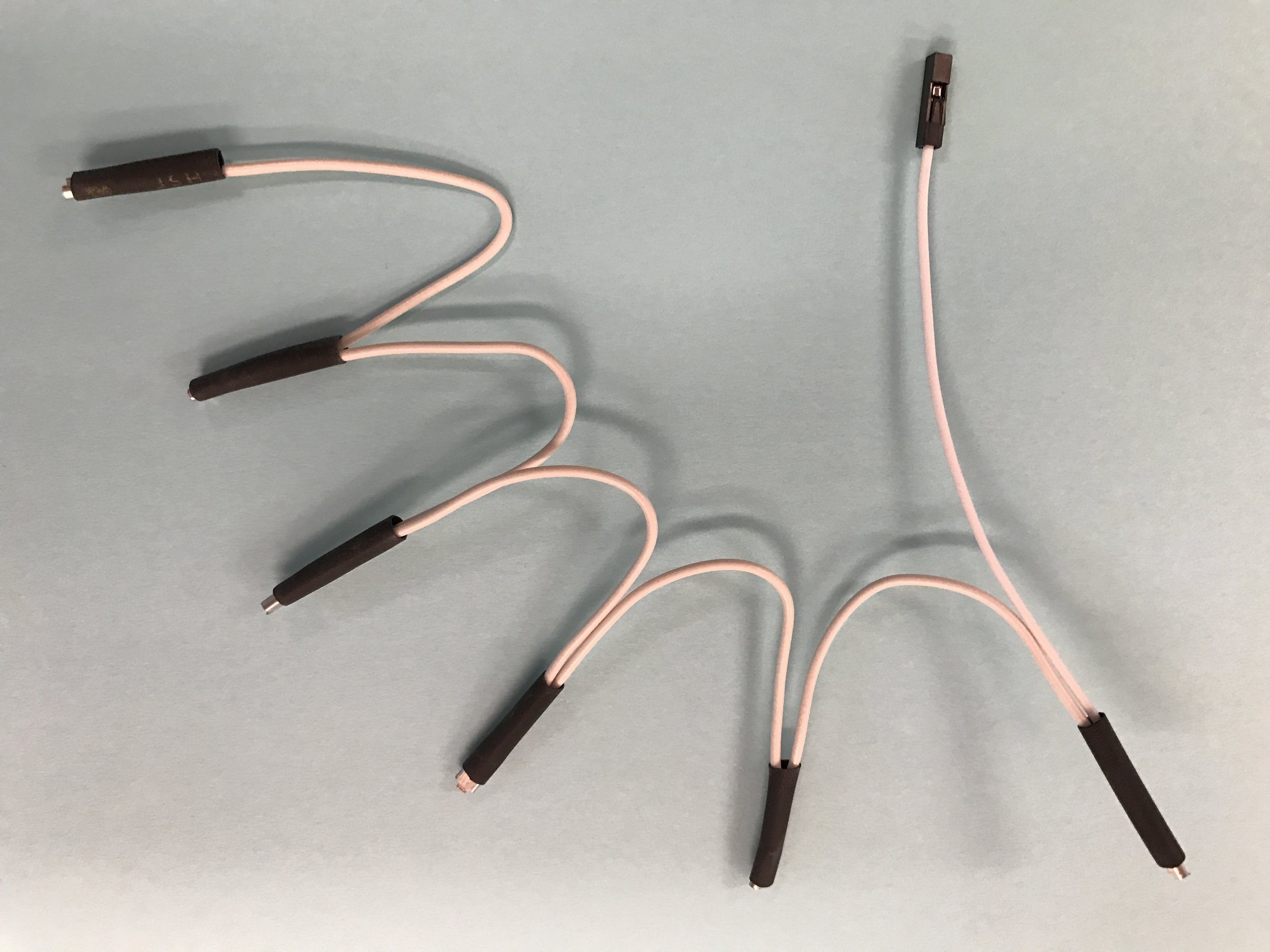 """- Attach the four remaining lengths of wire to create a chain, crimping together a new wire with the exposed bare end of the previous wire.One bare wire will remain at the end. Put a crimp on that bare wire.Cut six 2cm (3/4"""") long pieces of insulator tube; gently push it over each of the crimped ends of the daisy chain.Your final chain will include six crimped ends and one white plastic jumper end."""