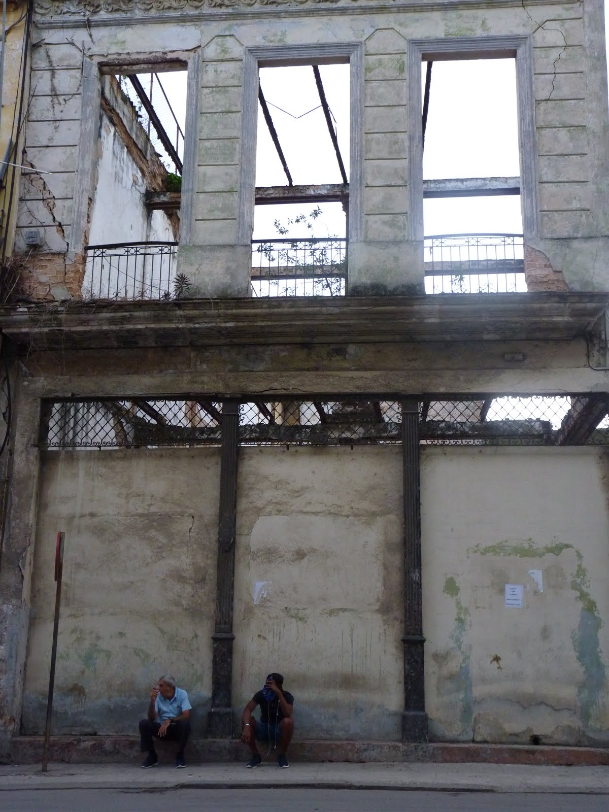 Two men sit on the curb of a remaining structure of a building in the old part of Havana. The structure was solely supported by the erection of the interior metal framework - a common place for cats to lounge, as well.