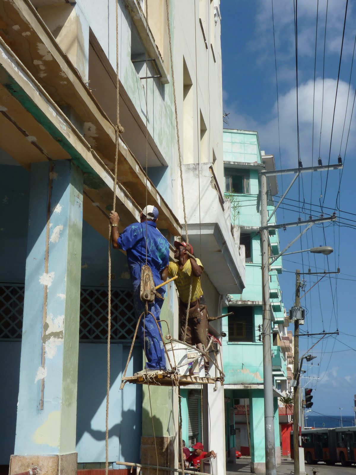 Two men working on a building.