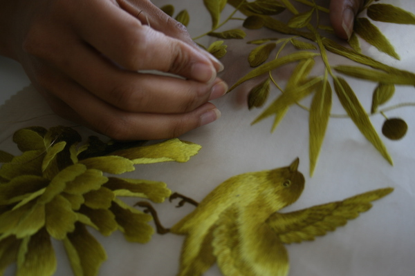A Fromental wallcovering being hand-embroidered with incredible skill
